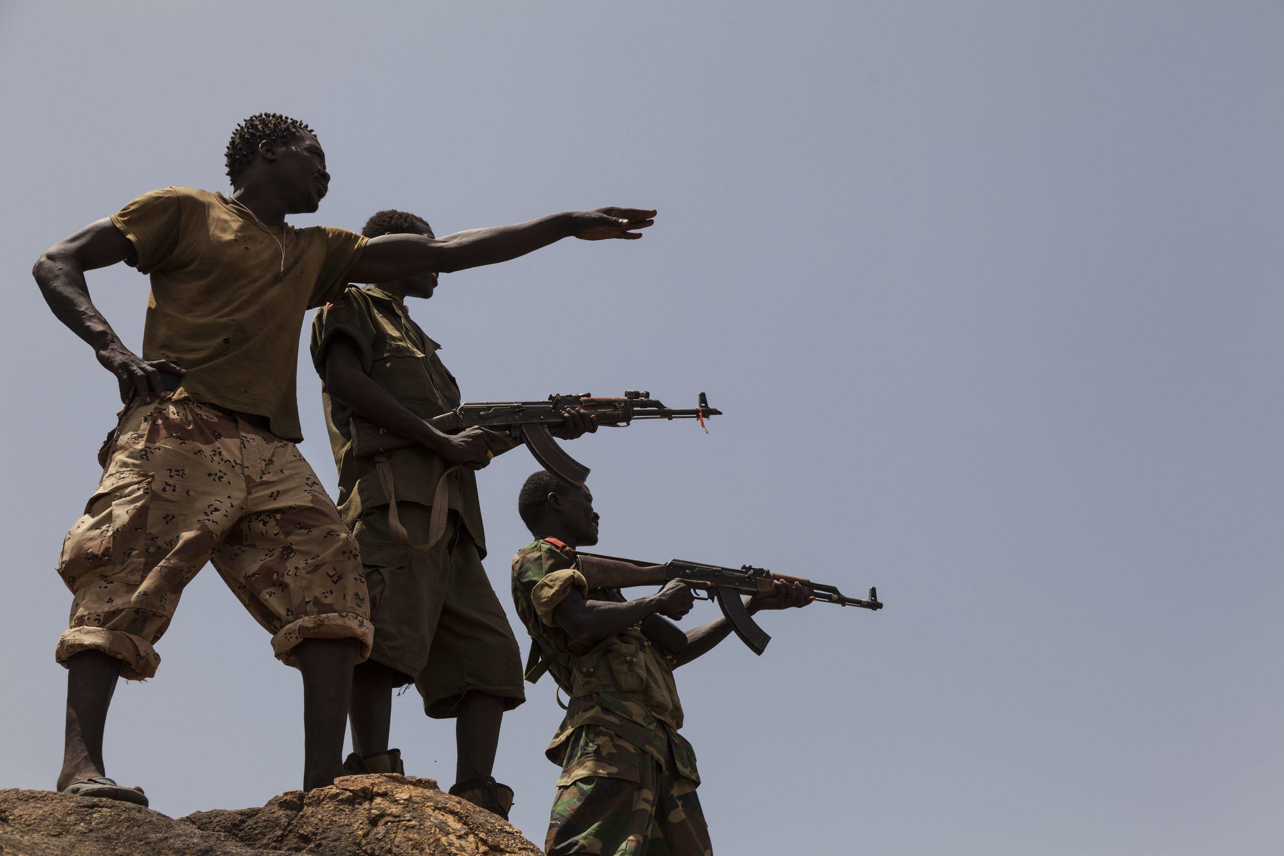 جنود من الجيش الشعبي  لتحرير السودان - قطاع الشمال يشيرون إلى قوات الحكومة السودانية من أعلى جبل في جنوب كردفان، 25 أبريل 2012