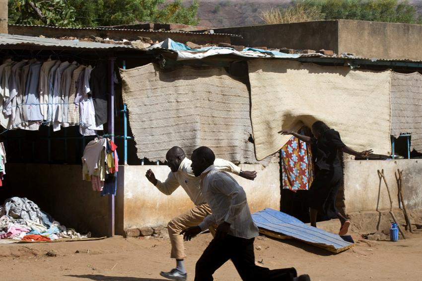 أشخاص يركضون للاختباء خلال القصف على بلدة كاودا