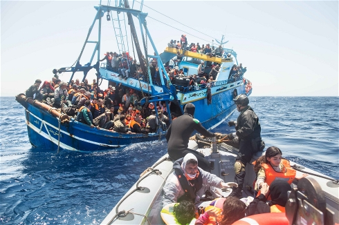 Migrants packed aboard a fishing boat are rescued by the Italian navy (Massimo Sestini/The Italian Coastguard)