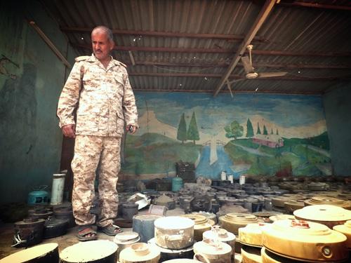 الشيخ زيد ثابت، رئيس برنامج مكافحة الألغام في عدن، يقف وسط بعض الألغام الأرضية التي عثرت عليها الفرق التابعة له منذ منتصف يوليو