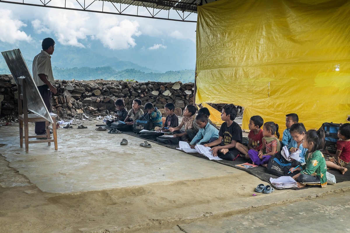Children attend a class where their school once stood on 10 August 2015 in Sipa Pokhari. The school now only has one temporary learning center set up by NGOs, which has just two classrooms. The rest of the students attend classes underneath a metal rooftop, with no walls and only tarps to separate each classroom.