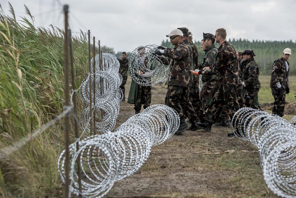جنود يقومون ببناء السياج في فترات عمل يصل طول كل منها 6 ساعات، لمدة 12 ساعة يومياً. وتقوم بصناعة السلك مجموعة من المساجين في بلدة دوناويفاروش التي تشتهر بصناعة الصلب