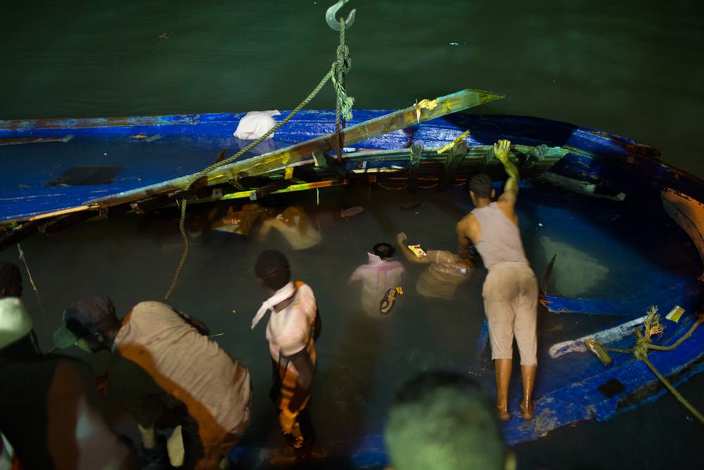 أثناء قطر القارب إلى الميناء، بدأت مهمة كئيبة لانتشال الجثث العالقة