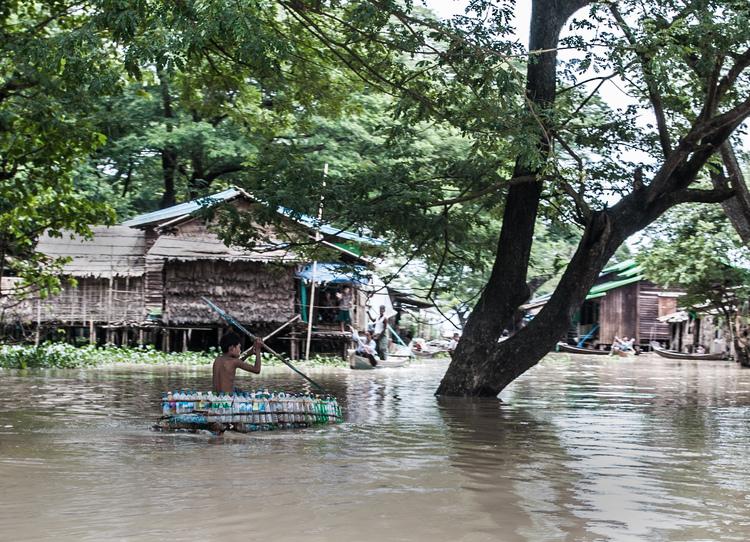 صبي يجدف في قارب مصنوع من القوارير البلاستيكية الفارغة في قرية سيت بين جيي، حيث اضطر السكان المحليون للبحث عن حلول للتعامل مع الفيضانات