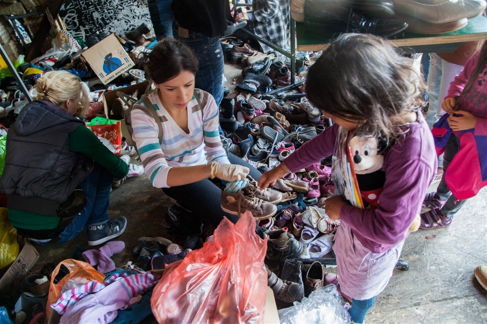 A volunteer helps a young Syrian girl find new shoes and socks at Miksaliste, a hub for the refugee response in Belgrade (James Haines-Young/IRIN)