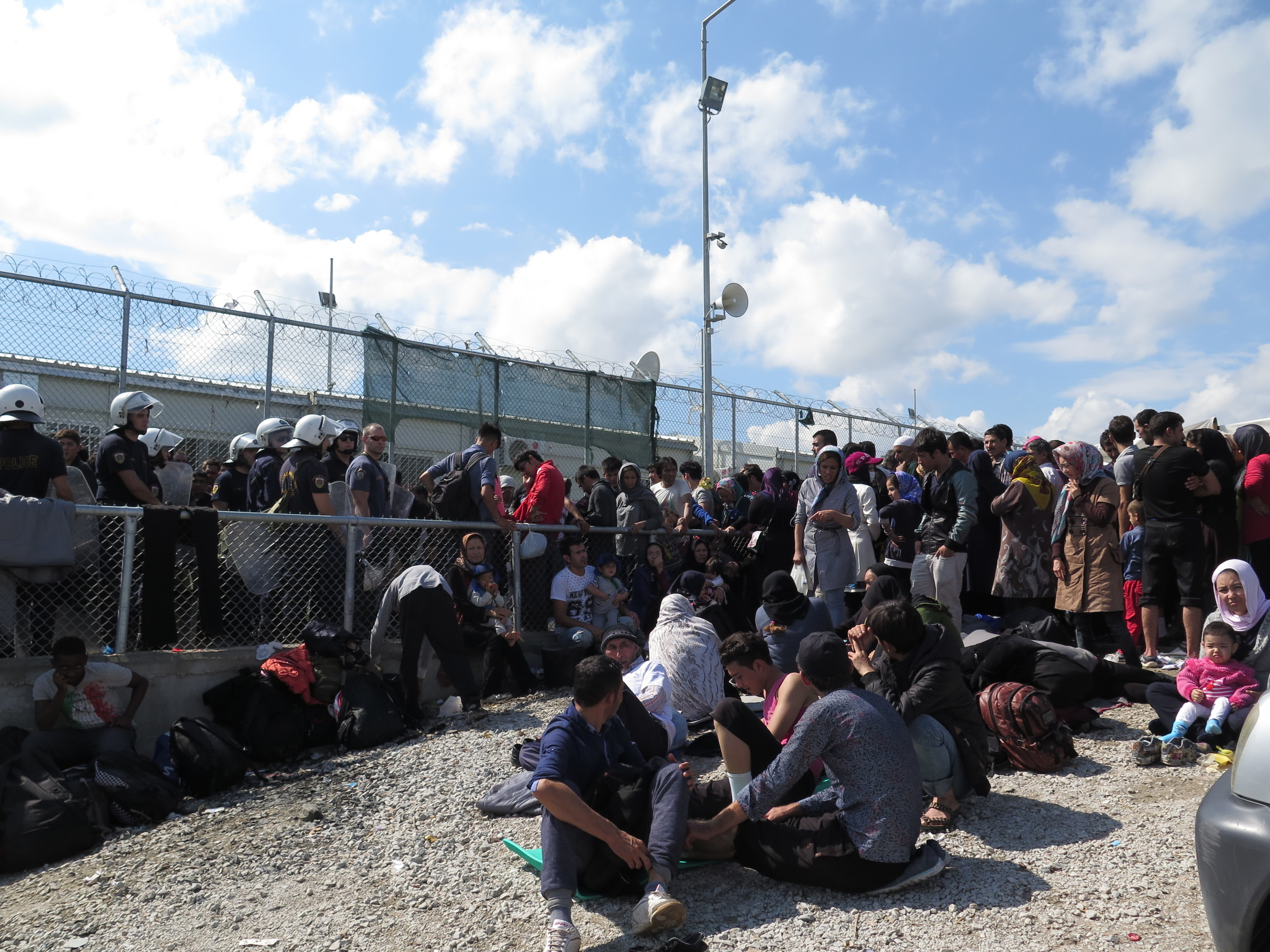 At Moria camp, Greek riot police push back non Syrian refugees from the barbed wire surrounding the registration centre. Here, people wait for hours in the hot sun before they can complete papers (Imogen Wall/IRIN)