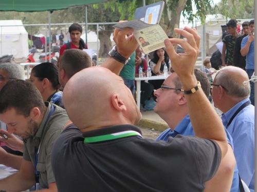 أحد مسؤولي فرونتكس في مخيم كارا تيبي يتحقق من جواز سفر سوري لمعرفة ما إذا كان أصلياً. ويشهد المسؤولون هنا عدداً متزايداً من الوثائق السورية المزورة (ايموجين وول/إيرين)