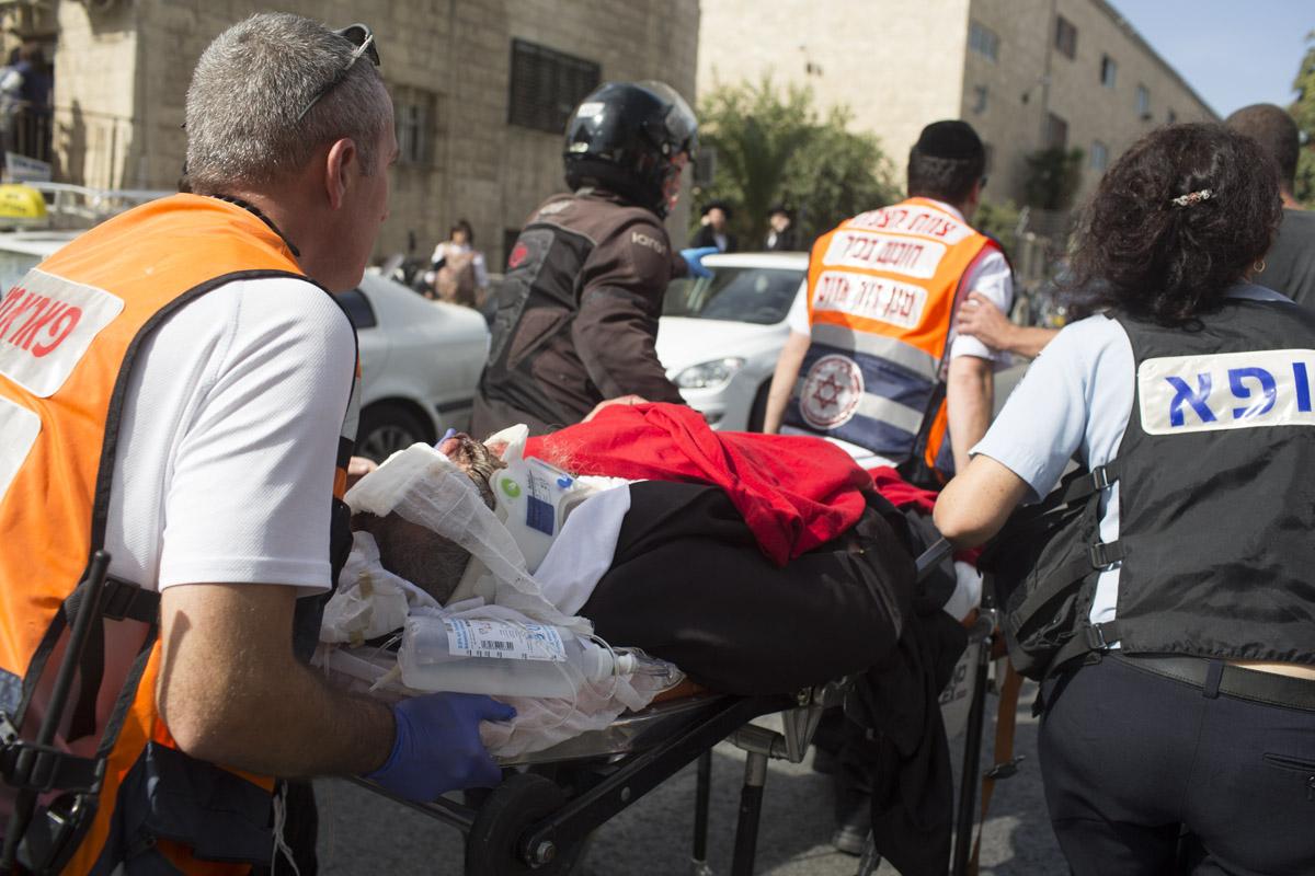 مستجيبون إسرائيليون يقومون بنقل الجرحى بعد قيام أحد الأشخاص بمهاجمة موقف للحافلات في حي للمتطرفين الدينيين في القدس بسيارته في الأسبوع الماضي.