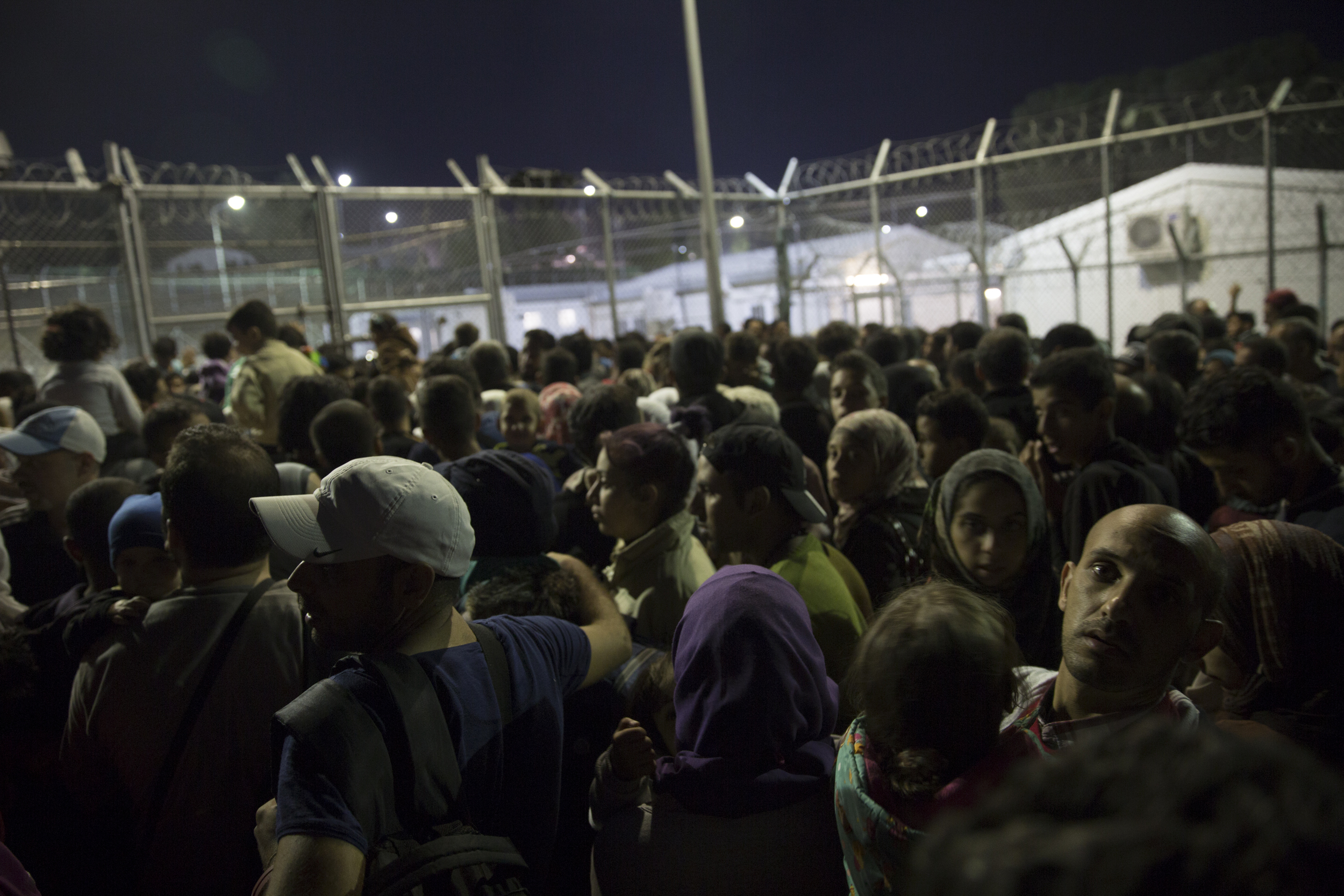 Refugees wait outside Moria, a former detention centre, to be fingerprinted and registered