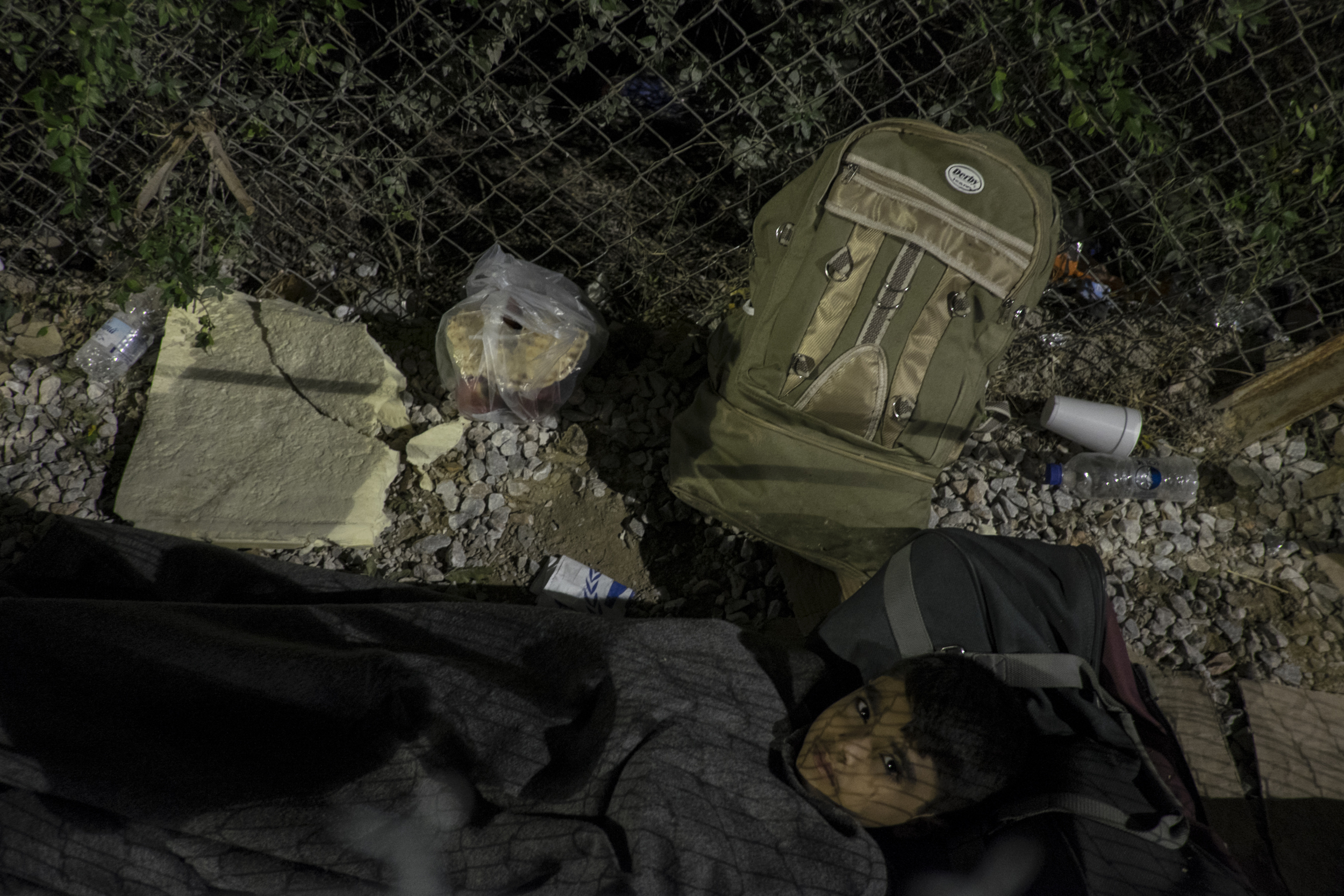 A boy, who is by himself, tries to sleep on a piece of cardboard next to the fence outside Moria reception centre