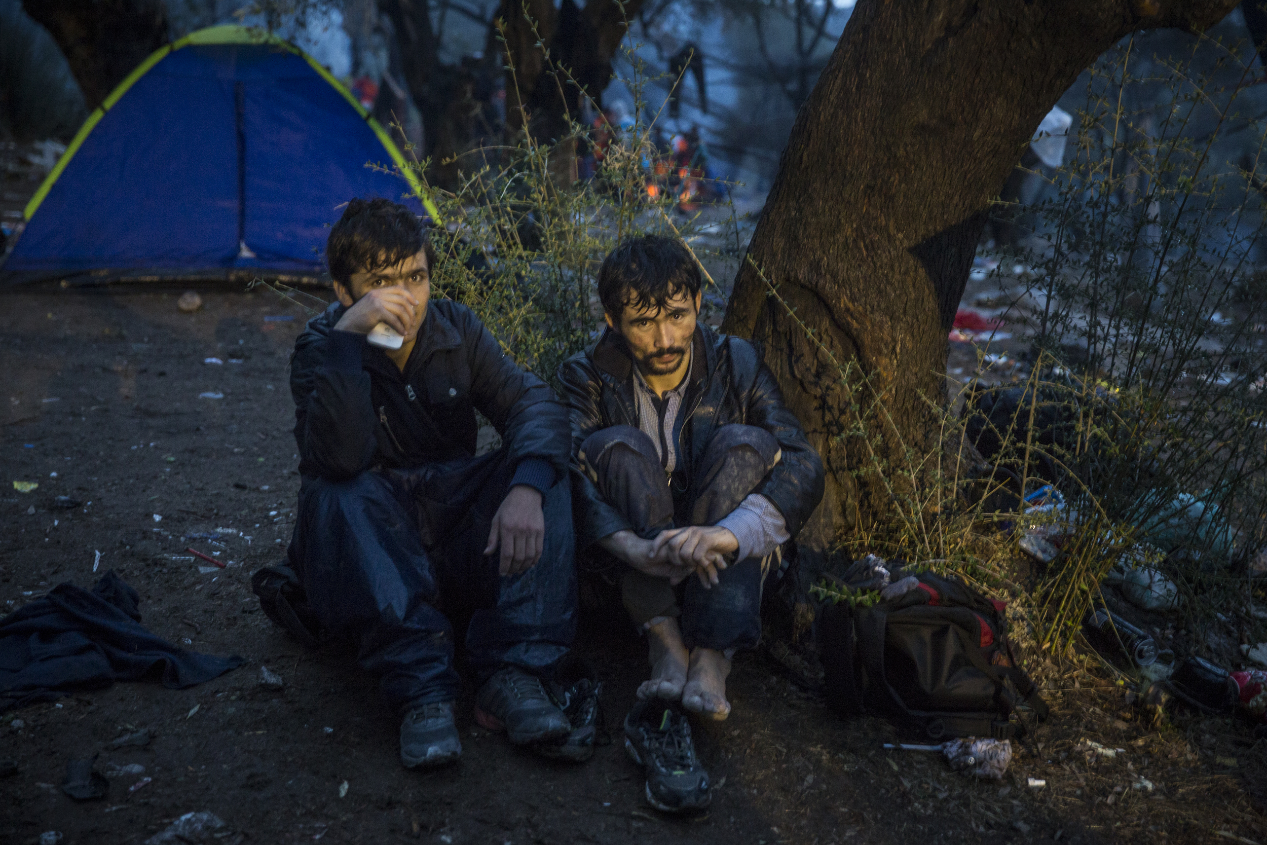 Two Afghan refugees camp in the rain outside Moria