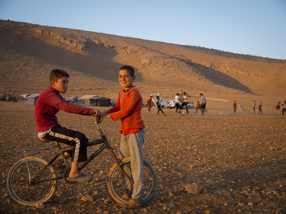 مجموعة شبان يلعبون مباراة كرة قدم على قمة الجبل، في الوقت الذي تدور في أسفله معركة للسيطرة على مدينة سنجار.