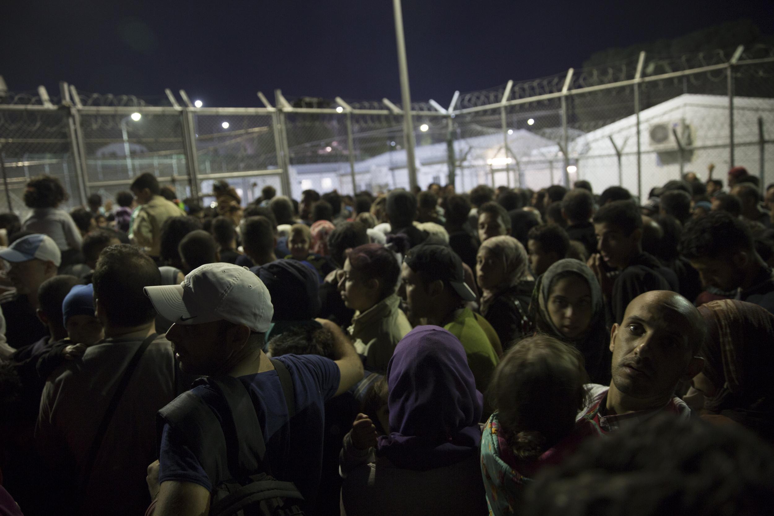 Des réfugiés attendent d'être enregistrés et de laisser leurs empreintes digitales, à l'extérieur du centre de détention de Moria
