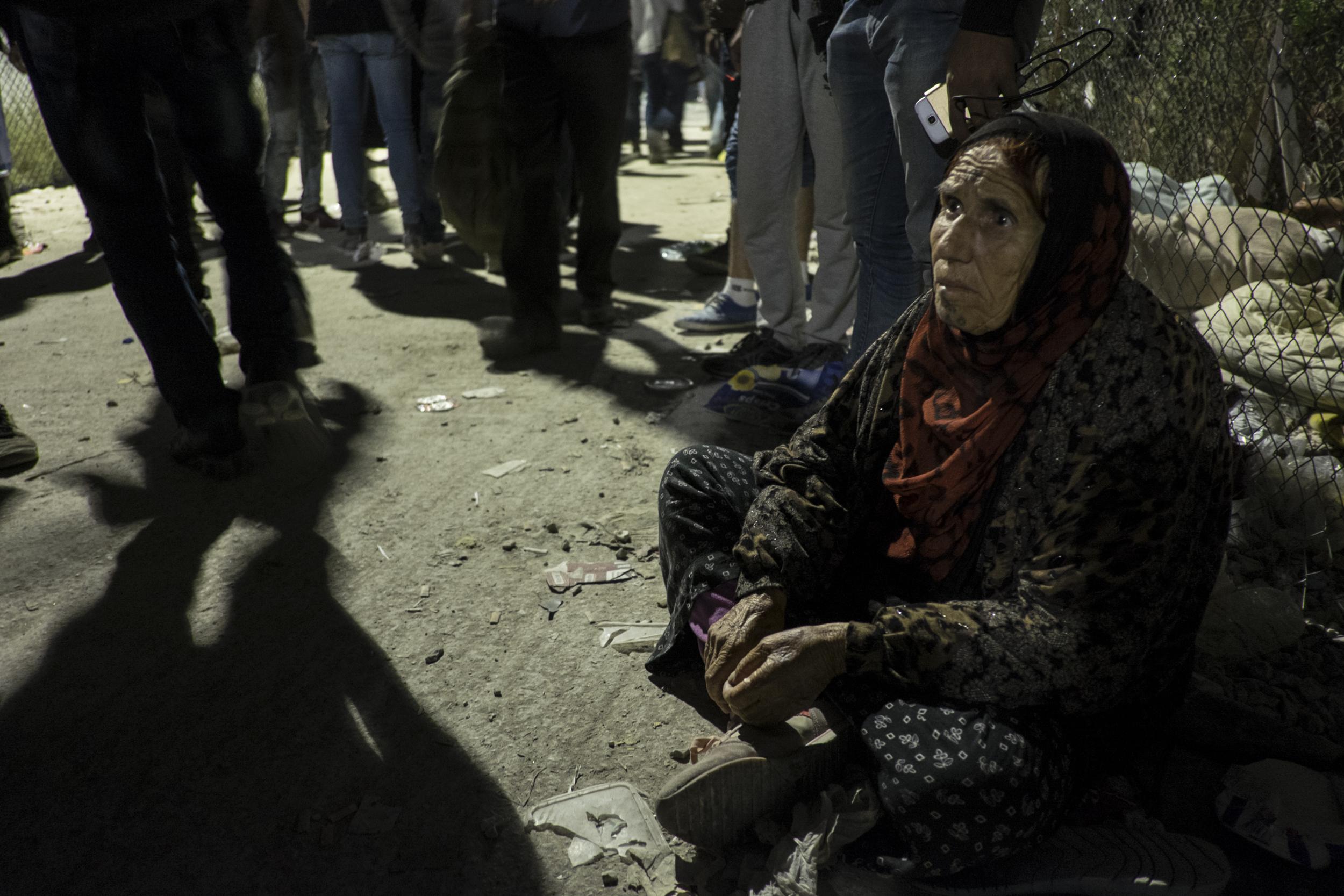 Une vieille femme kurde de Syrie, à l'extérieur de Moria. Les personnes âgées et les handicapés perdent souvent leur place dans la queue