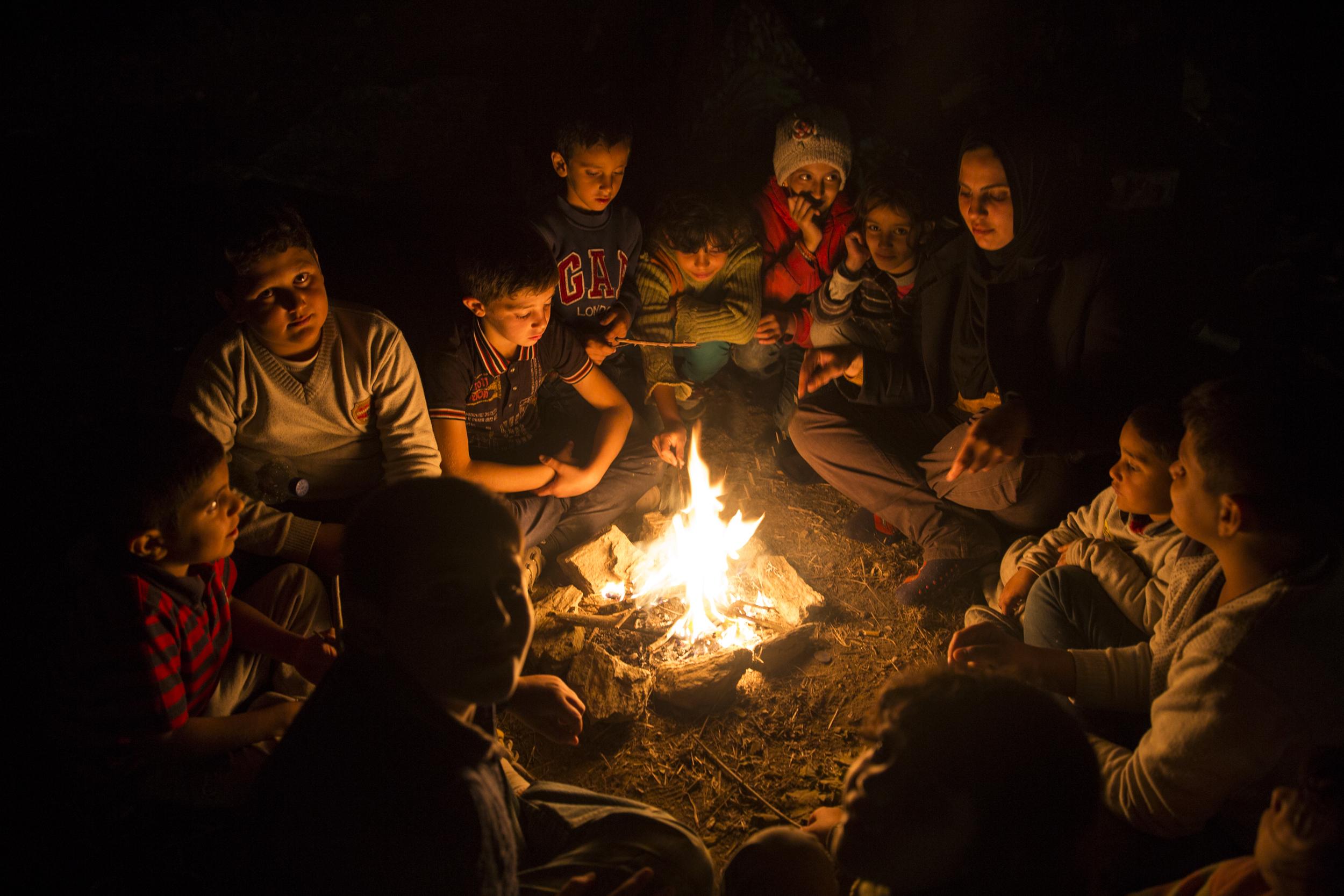 Des enfants rassemblés autour d'un feu, dans les oliveraies à l'extérieur de Moria où des centaines de personnes ont monté le camp ces derniers jours en attendant d'être enregistrées
