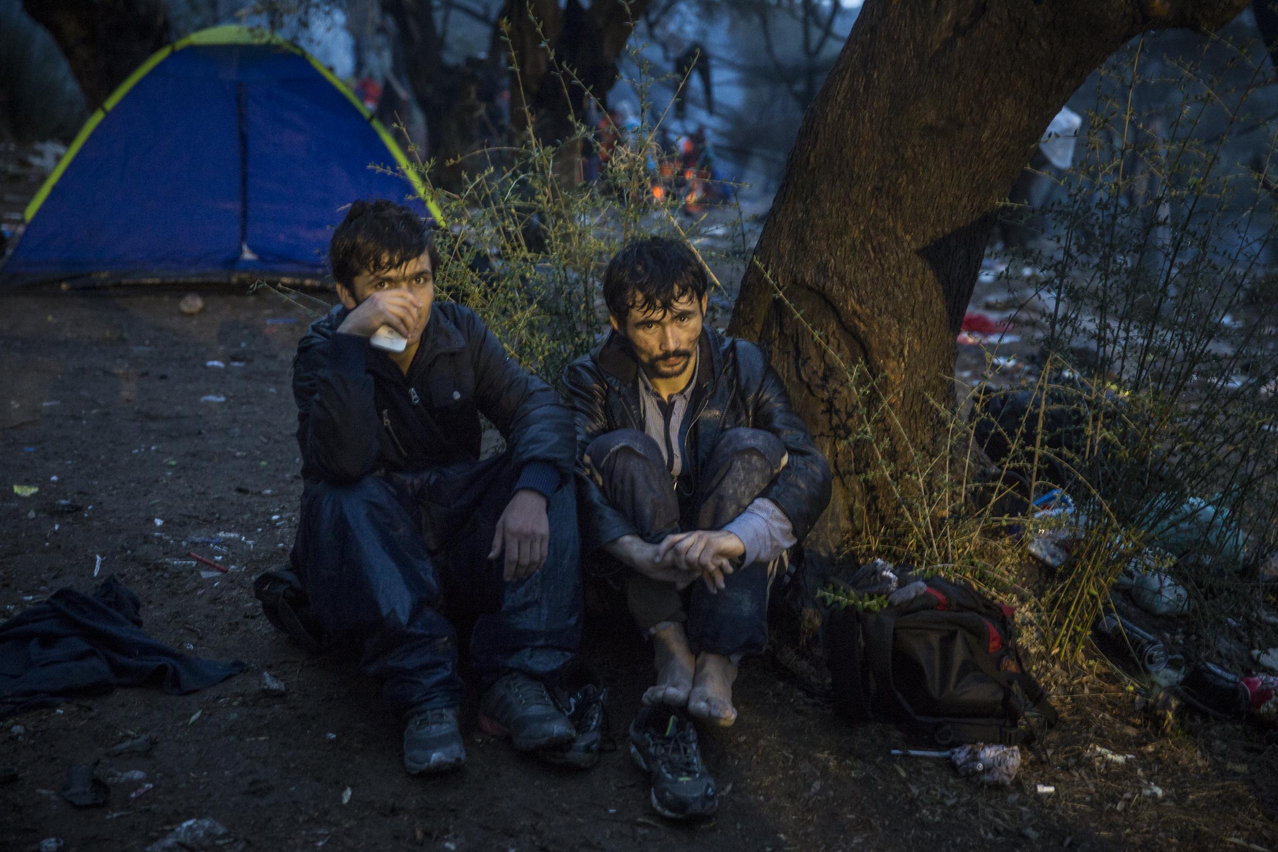 Deux réfugiés afghans campent sous la pluie, à l'extérieur de Moria