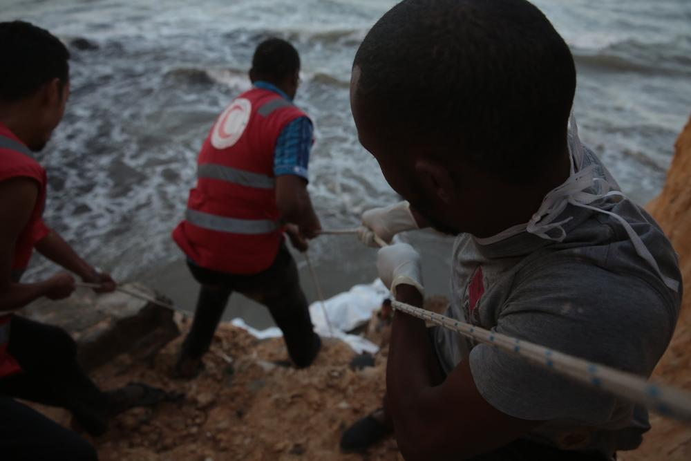 متطوعو الهلال الأحمر الليبي يستخدمون الحبال لسحب جثة مهاجر إلى قمة منحدر على شاطئ تاجوراء-إحدى ضواحي طرابلس (محمد بن خليفة/إيرين)
