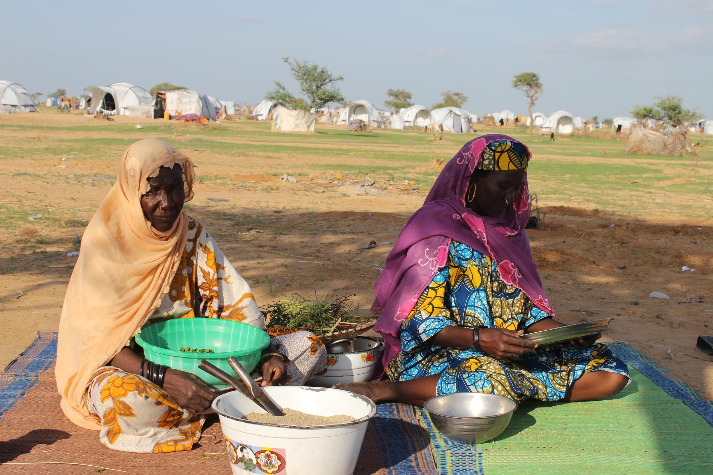 Nigerian refugees prepare millet outside a refugee camp in Niger's Diffa region (Boureima Balima)