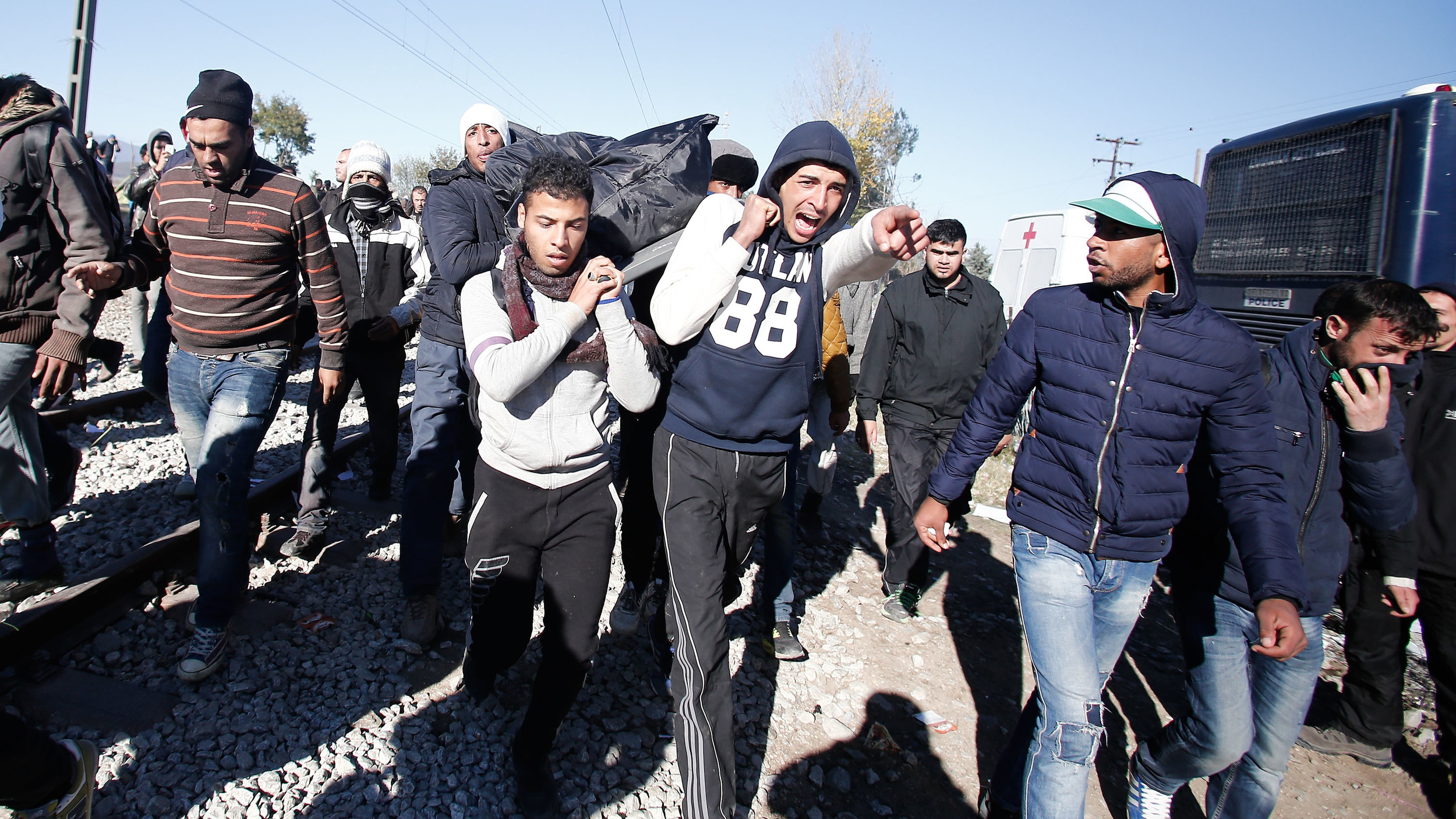 Morroccan migrants carry the body of their friend who was electrocuted after touching power cables