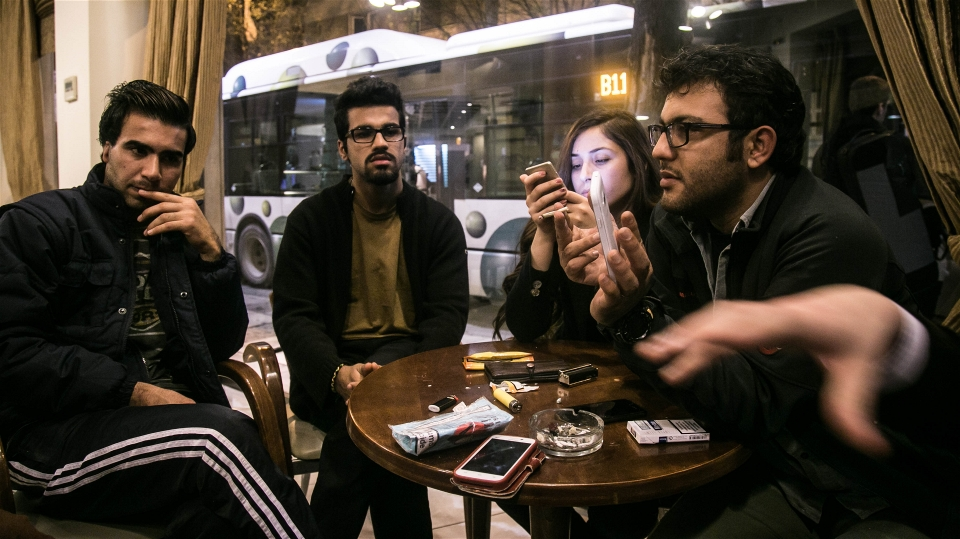 Aral Kakl (right), a Kurdish Iraqi journalist, his Syrian wife Shevin, his brother Rewan and some other refugees who have applied for the relocation programme, kill time in the cafeteria of their Athens hotel (Nicola Zolin/IRIN)