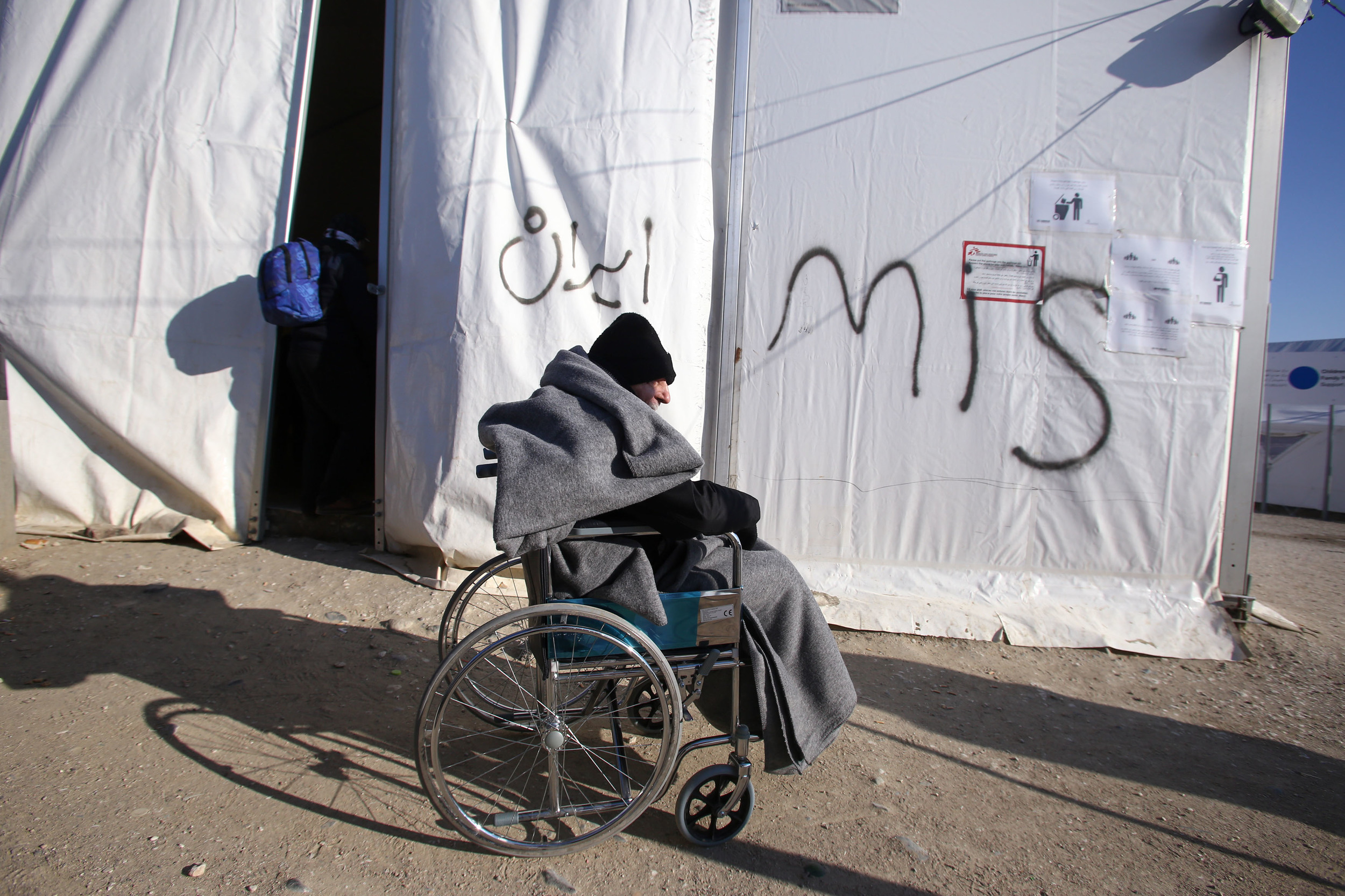 A disabled refugee, bundled up against the cold, outside one of the tents MSF has been allowed to erect outside the petrol station that has become a holding area for refugees and migrants trying to reach the border