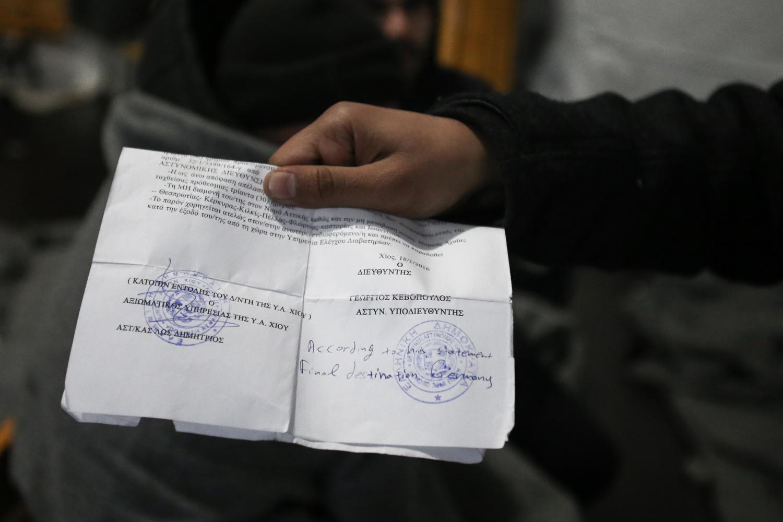 """لاجئ أفغاني يعرض وثيقة هويته اليونانية التي كتبت عليها الشرطة اليونانية: """"وفقاً لشهادته، الوجهة النهائية ألمانيا"""". وبحسب أحدث سياسة حدودية، يُسمح فقط للاجئين الذين يعلنون أن ألمانيا أو النمسا هي وجهتهم النهائية بعبور الحدود إلى مقدونيا"""