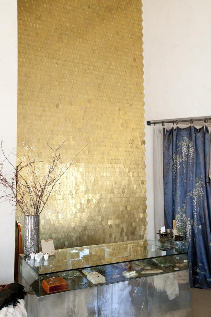 Gold Backsplash on a white wall at a Clothing Store provides interesting reflection depending on the time of the day