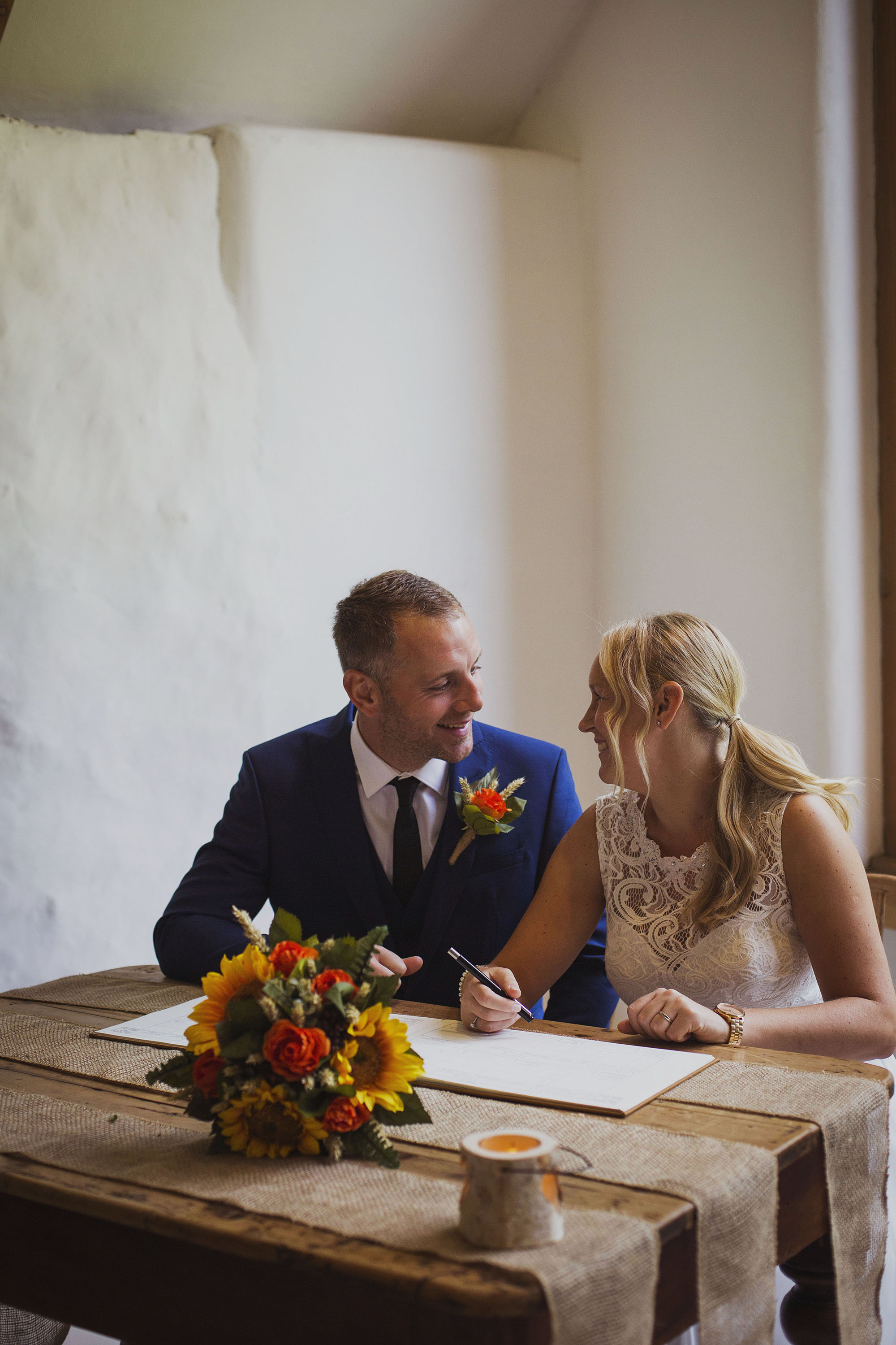 bride and groom sign the register at nantwen wedding venue