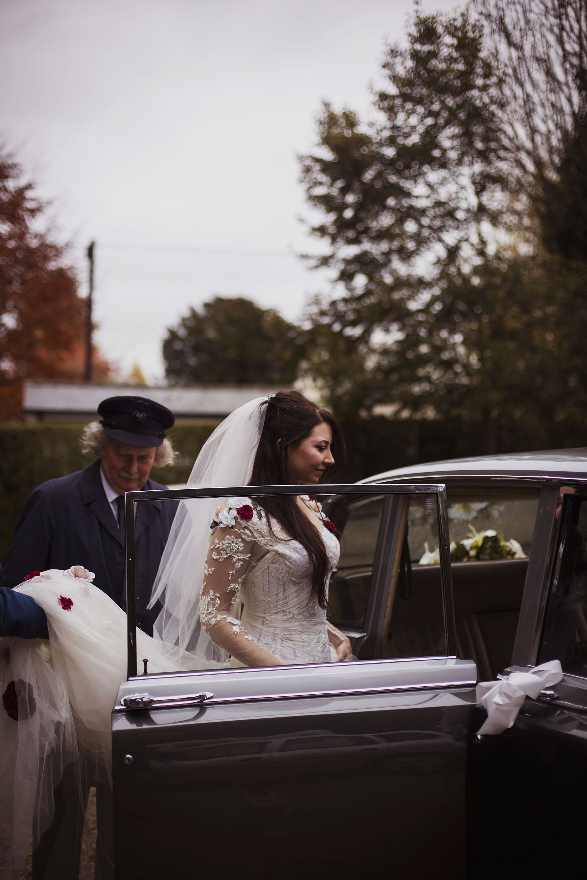 bride getting into car wearing veil at grasmere house hotel
