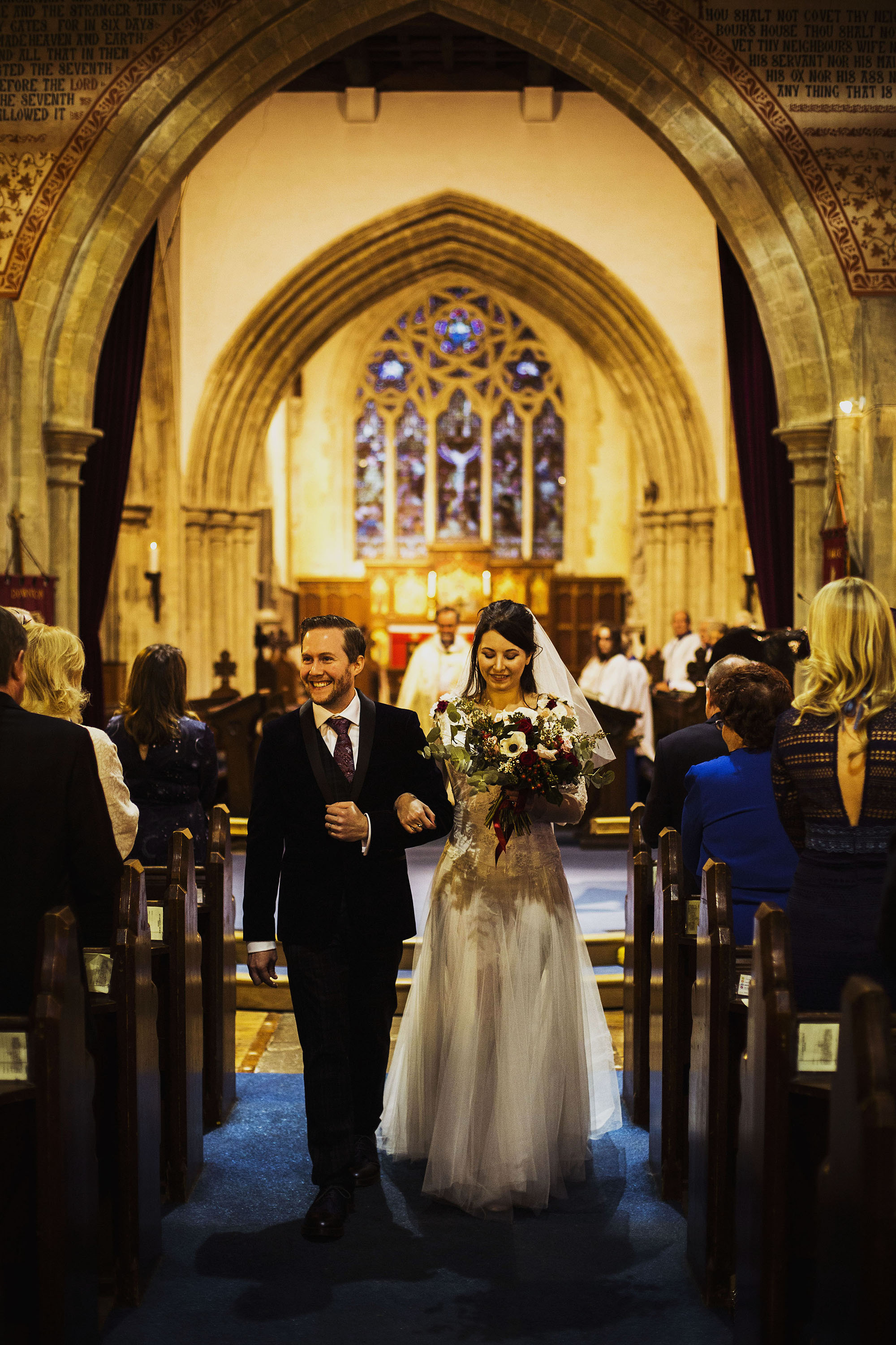 bride and groom walking down the isle at st laurence church