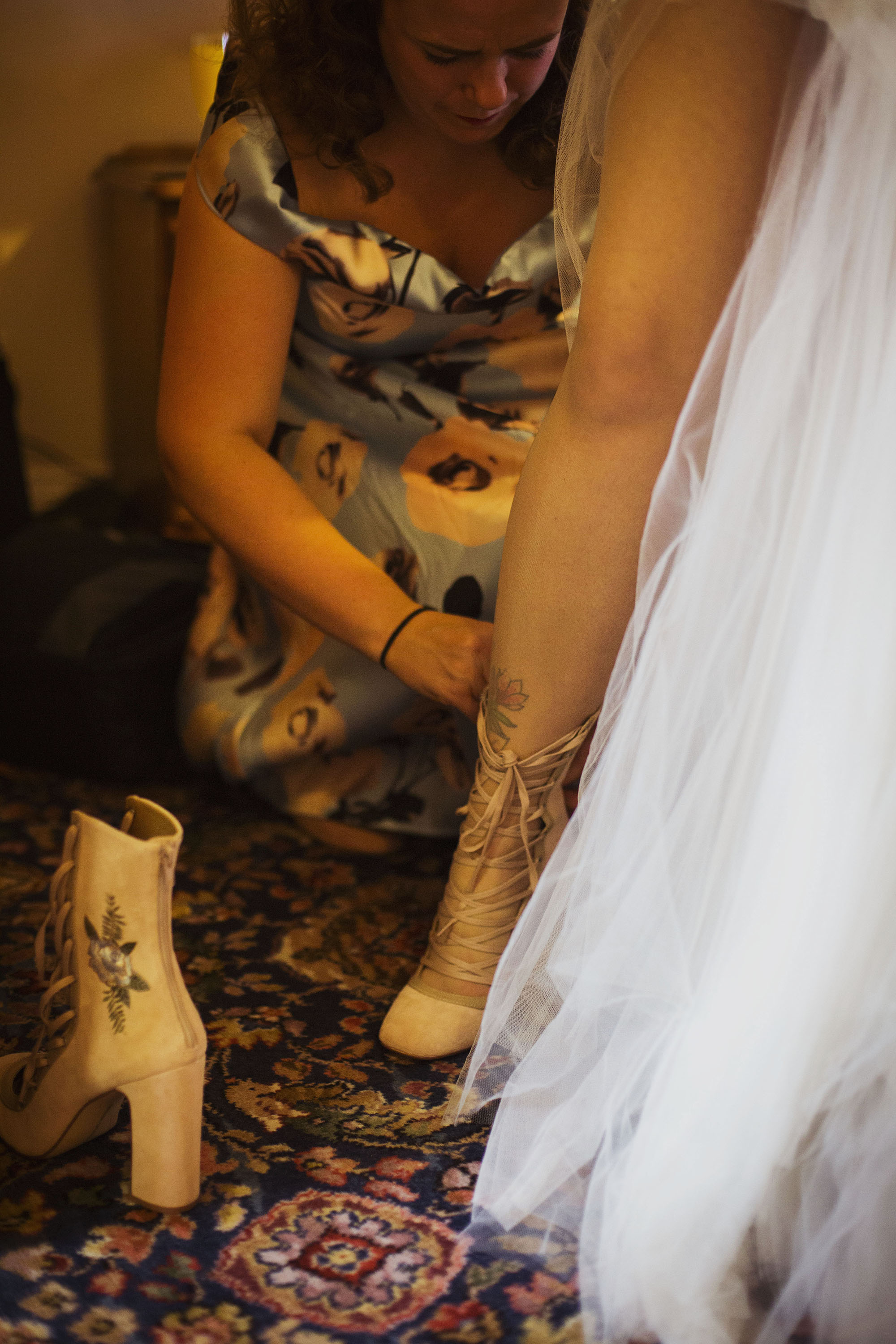 bridesmaid helping bride put her wedding shoes on at grasmere house hotel in salisbury