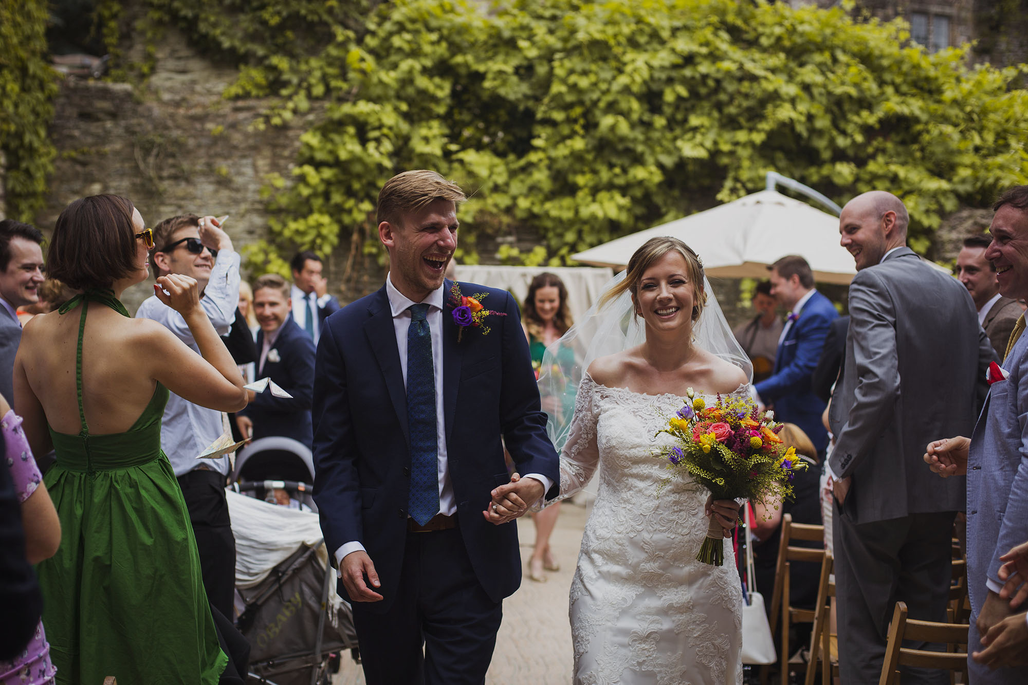 bride and groom smiling walking down the isle at usk castle