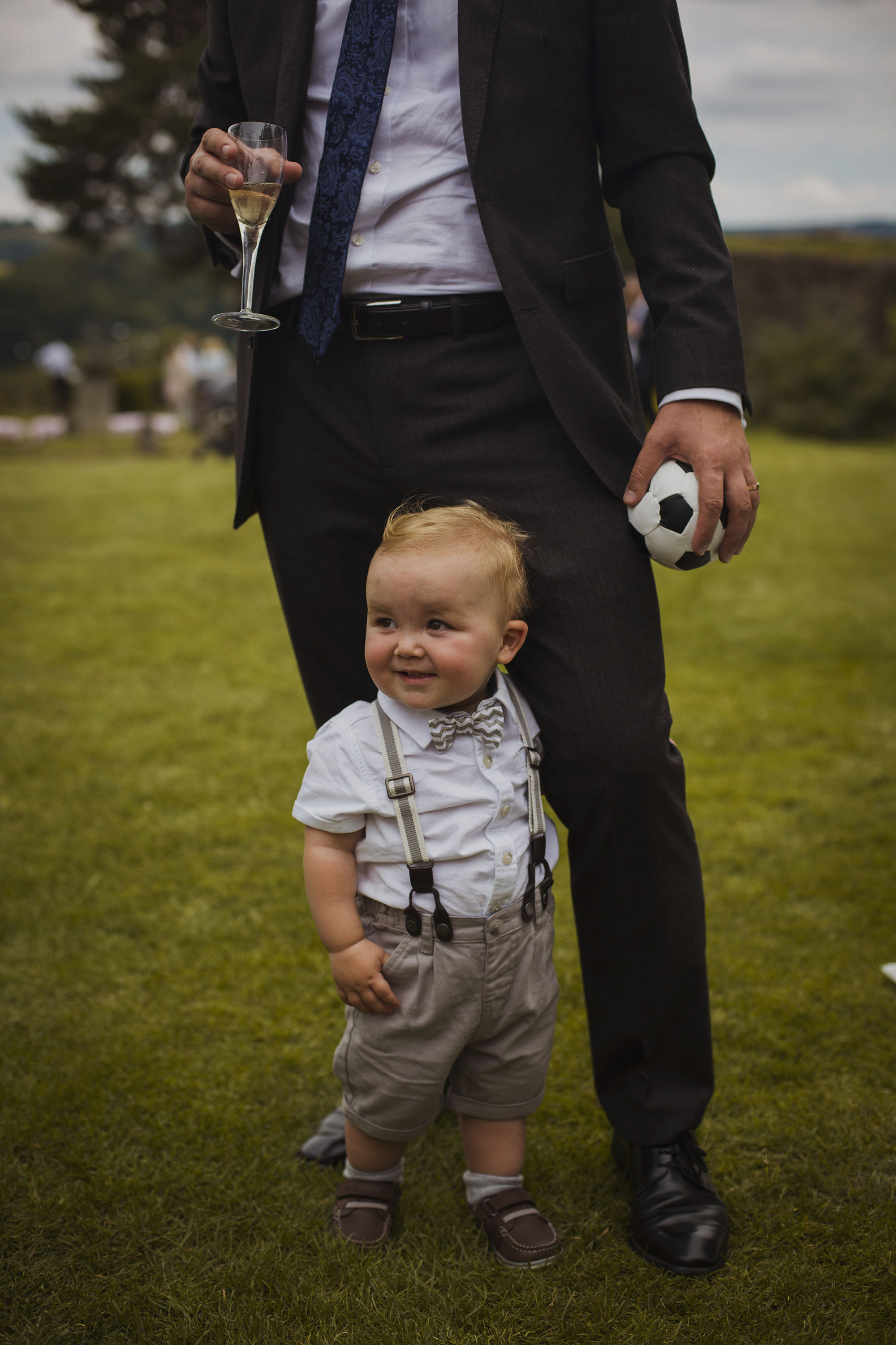 baby boy standing inbetween father's legs at wedding at usk castle