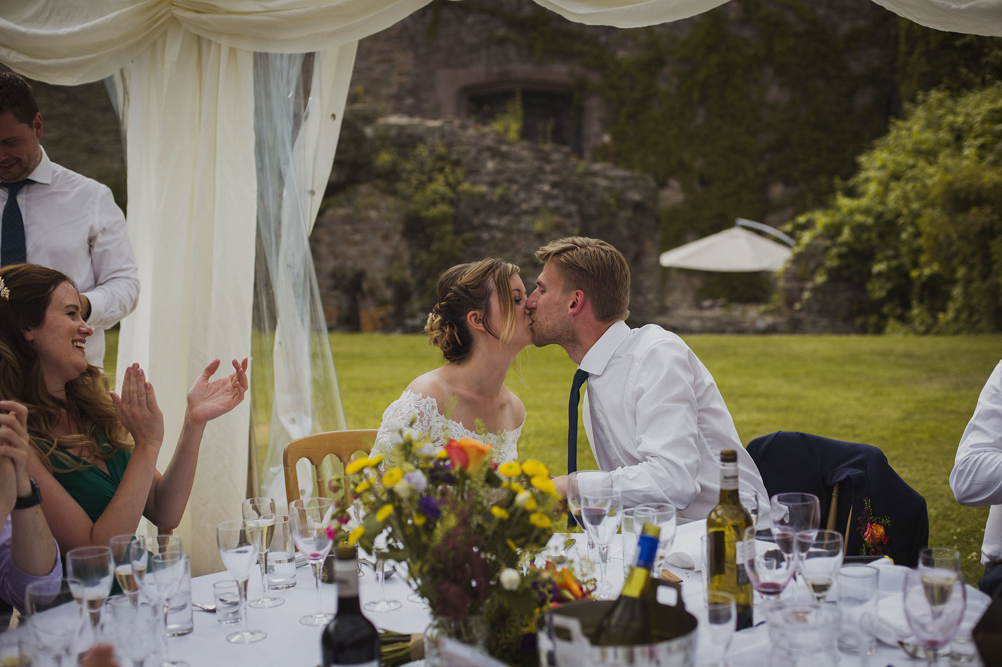bride and groom kissing during wedding speeches at usk castle