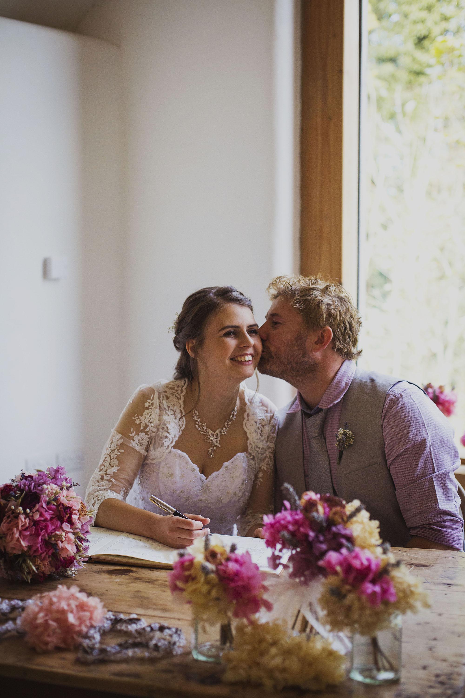 bride and groom signing the register at nantwen wedding venue