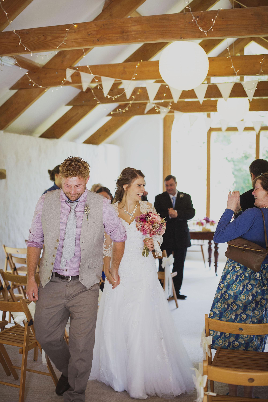 bride and groom walking down the isle just married at nantwen wedding venue