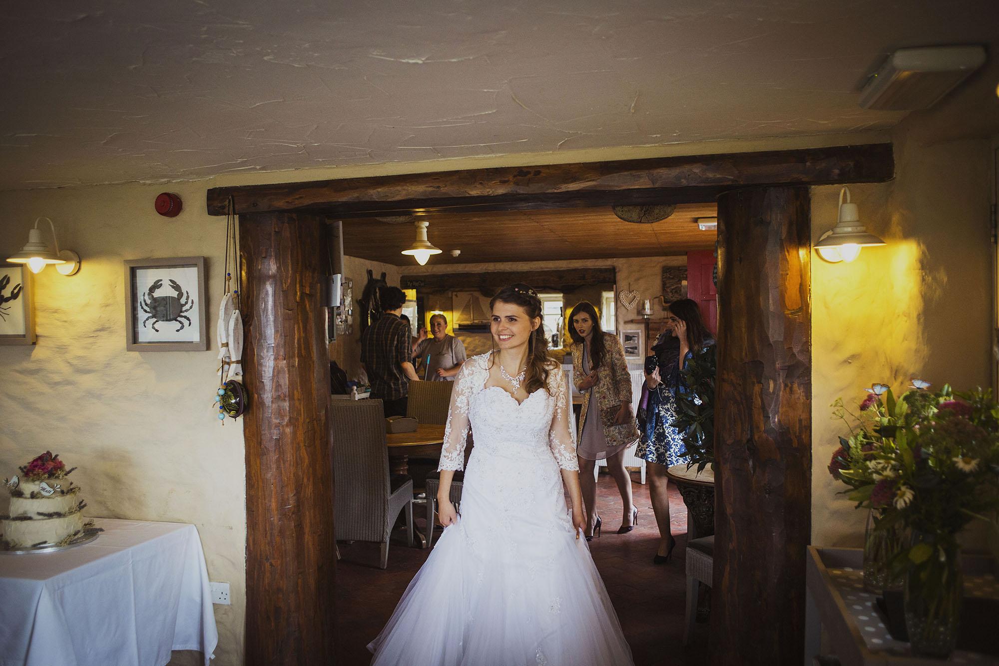 bride entering wedding dinner at the old sailors dinas cross newport pembrokeshire