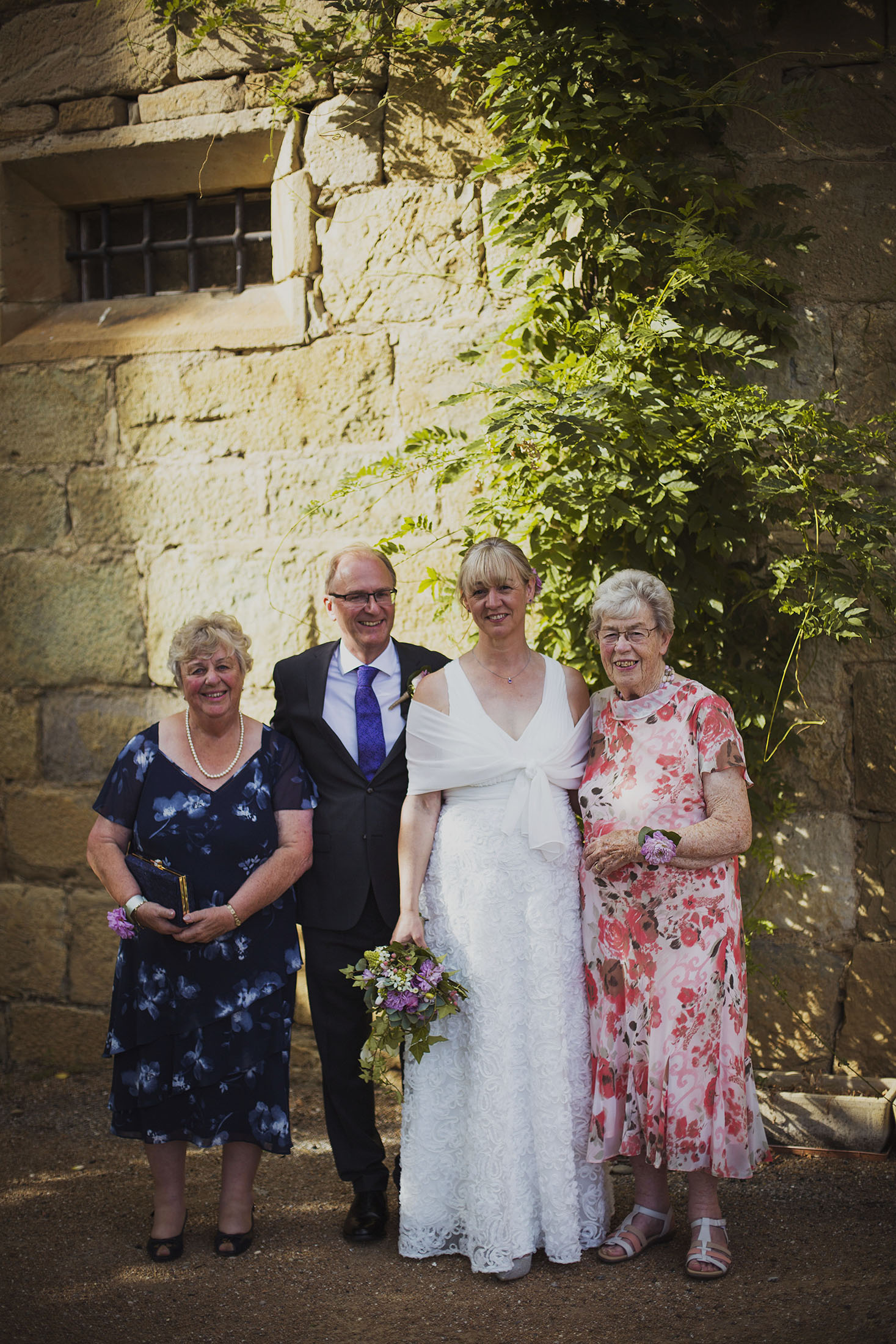 bride and groom with mothers at bridesmaids at chateaux des ducs de joyeuses france destination wedding photography