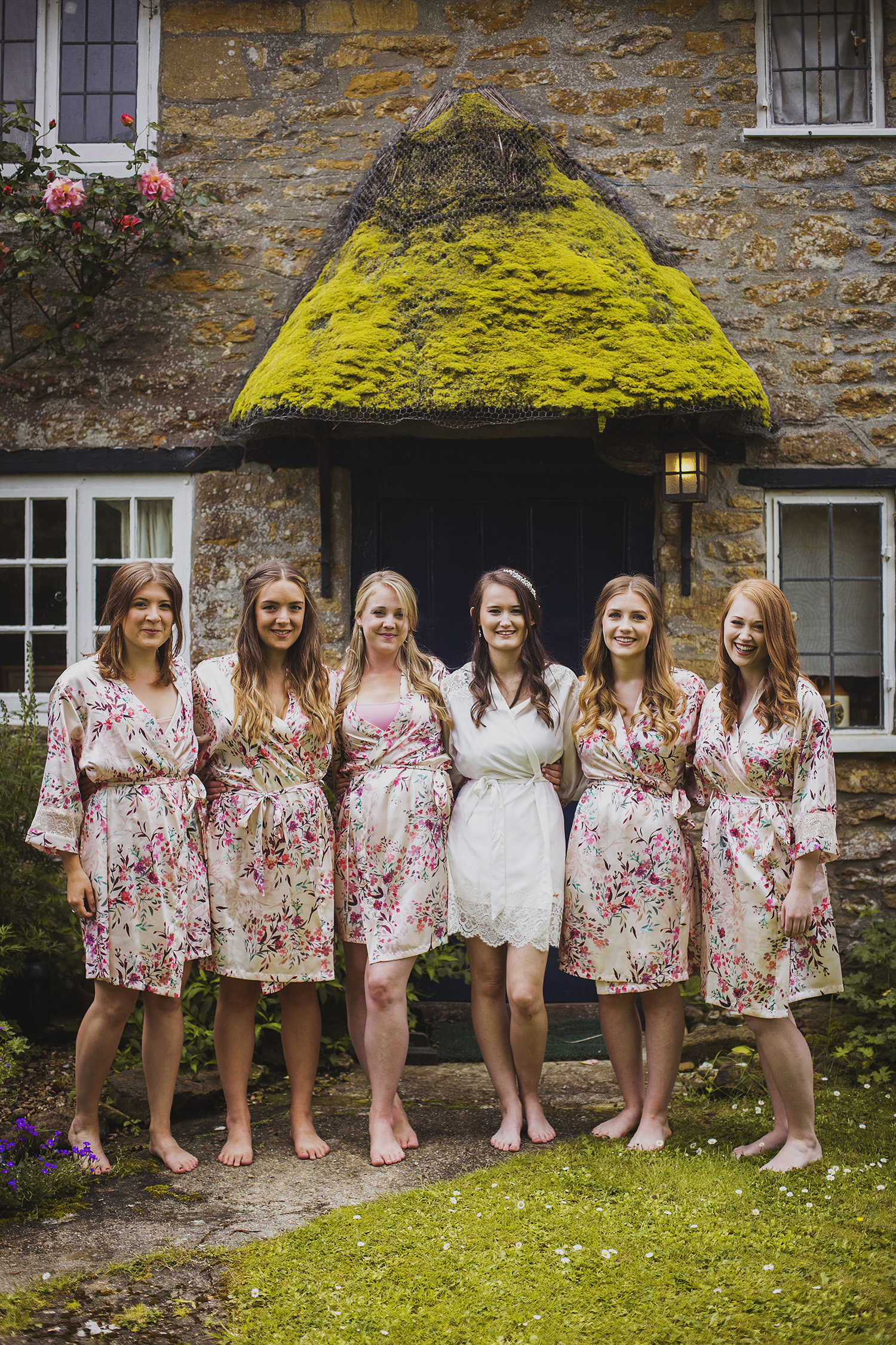 bride with bridesmaids outside cottage somerset wedding