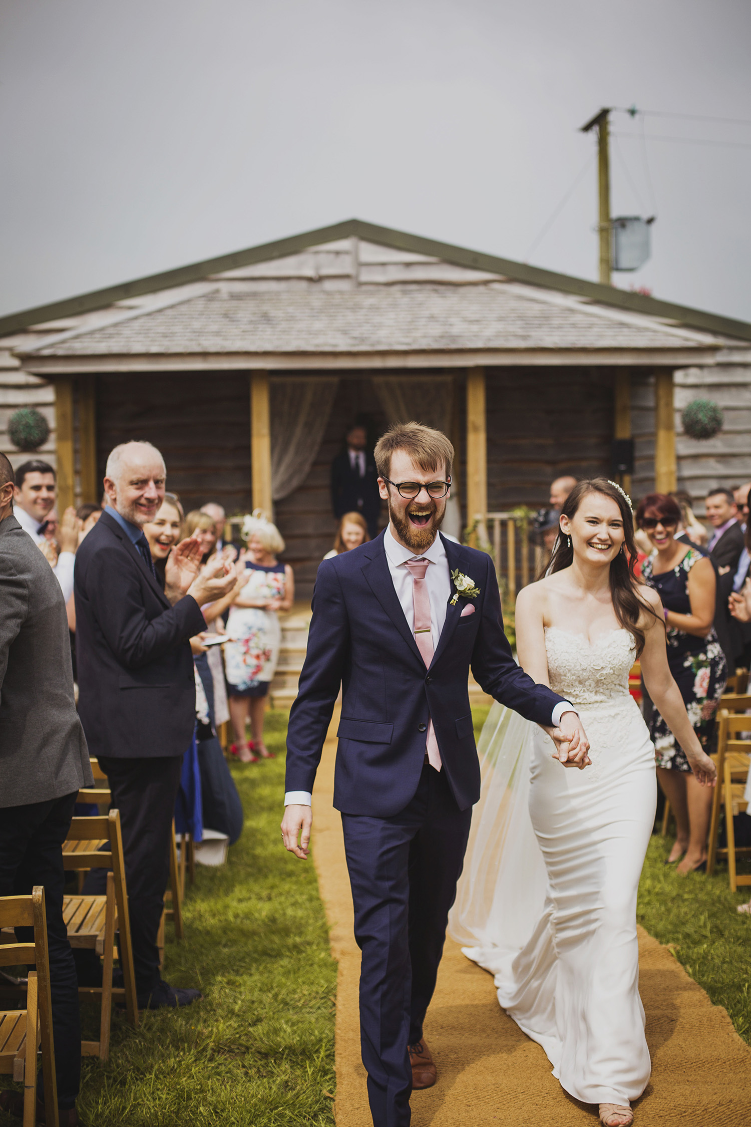 bride and groom walking down the isle at wedding ceremony at cott farm barn wedding venue somerset