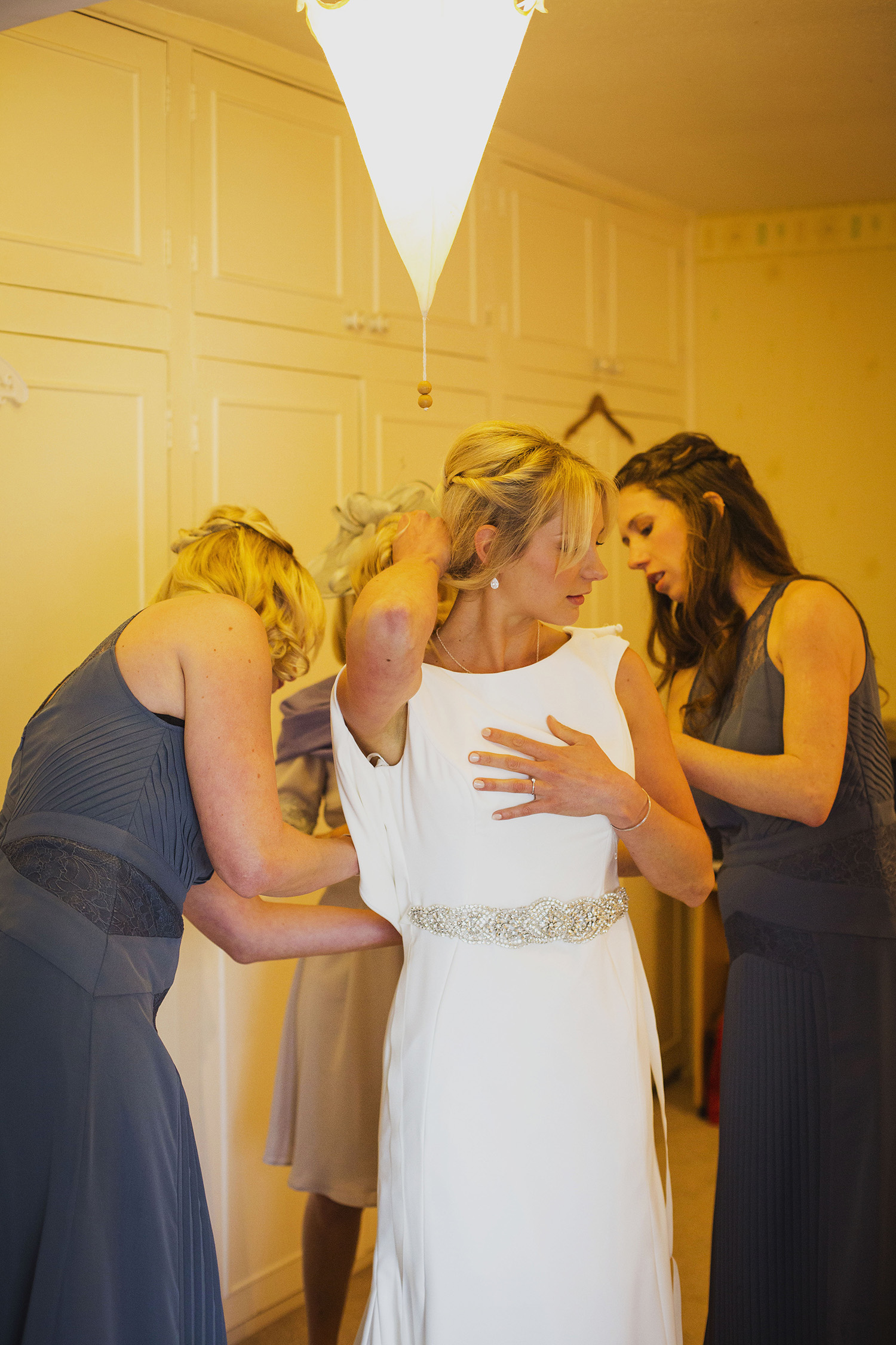 bride getting into dress at diy wedding in midlands