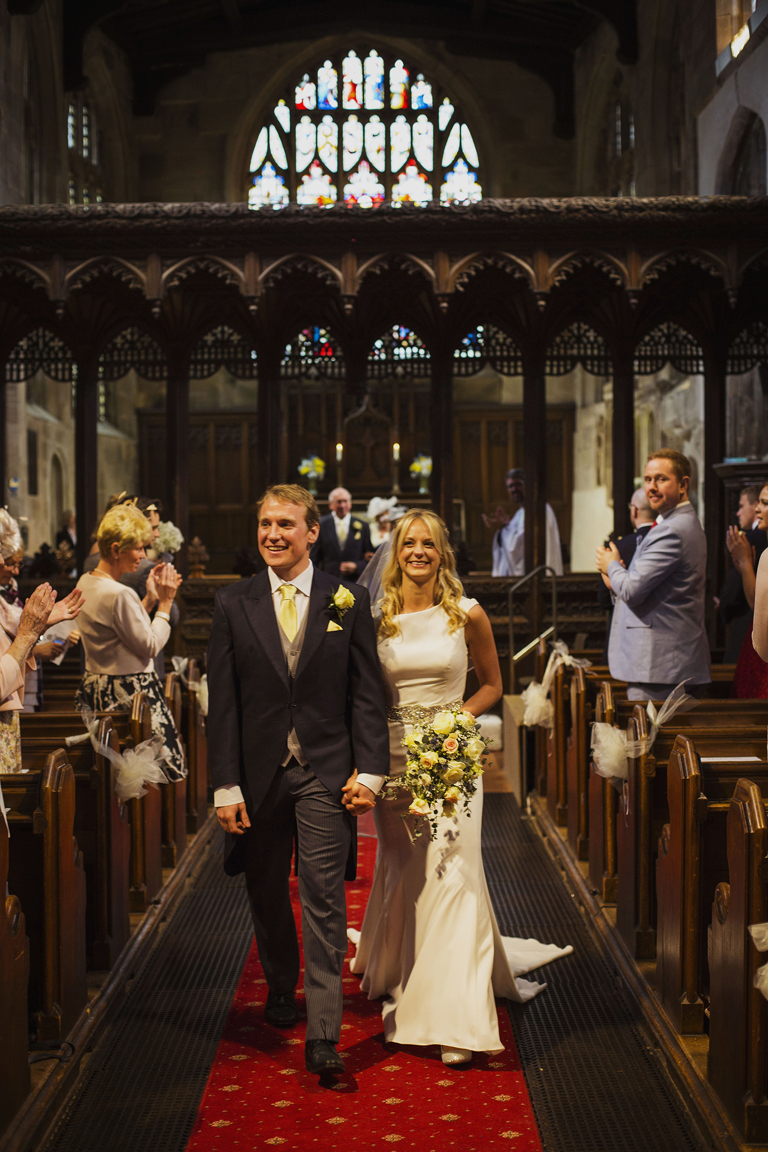 bride and groom walk down the isle at wedding ceremony at knowle parish church
