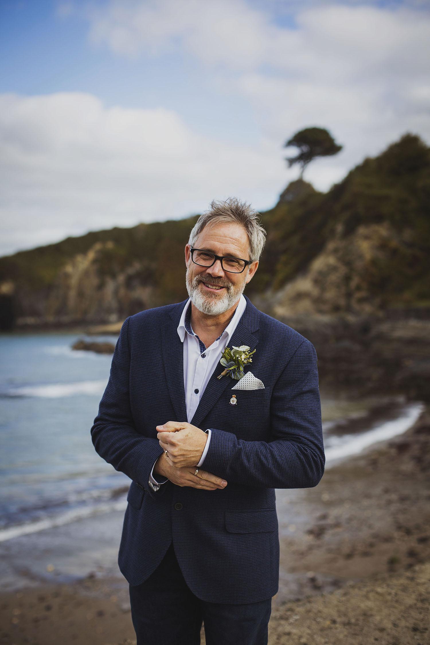 groom with flowers by annabel at beach nantwen wedding pembrokeshire wedding photographer