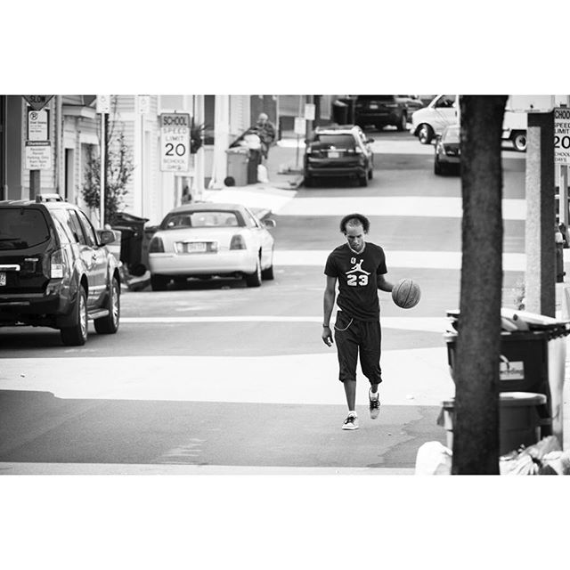 Candid moment in the streets of Boston. Like that this dude is presumably on his way to the court wearing a Jordan t-shirt but low top DC shoes to play in. Whatever works. #basketball#boston#streetphotography#nikon#basketballneverstops#sport#hoopdreams
