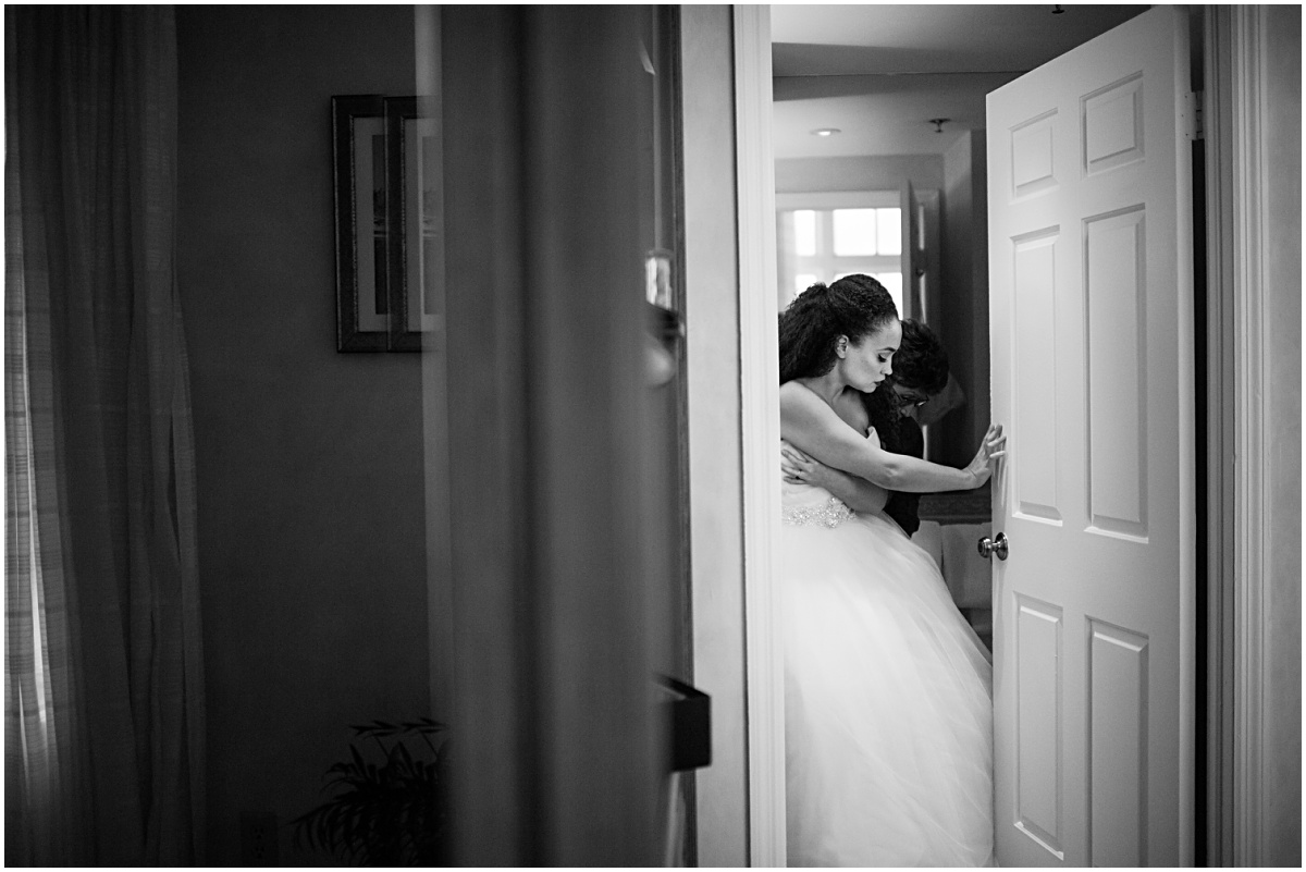 black and white candid moment of the bride getting ready
