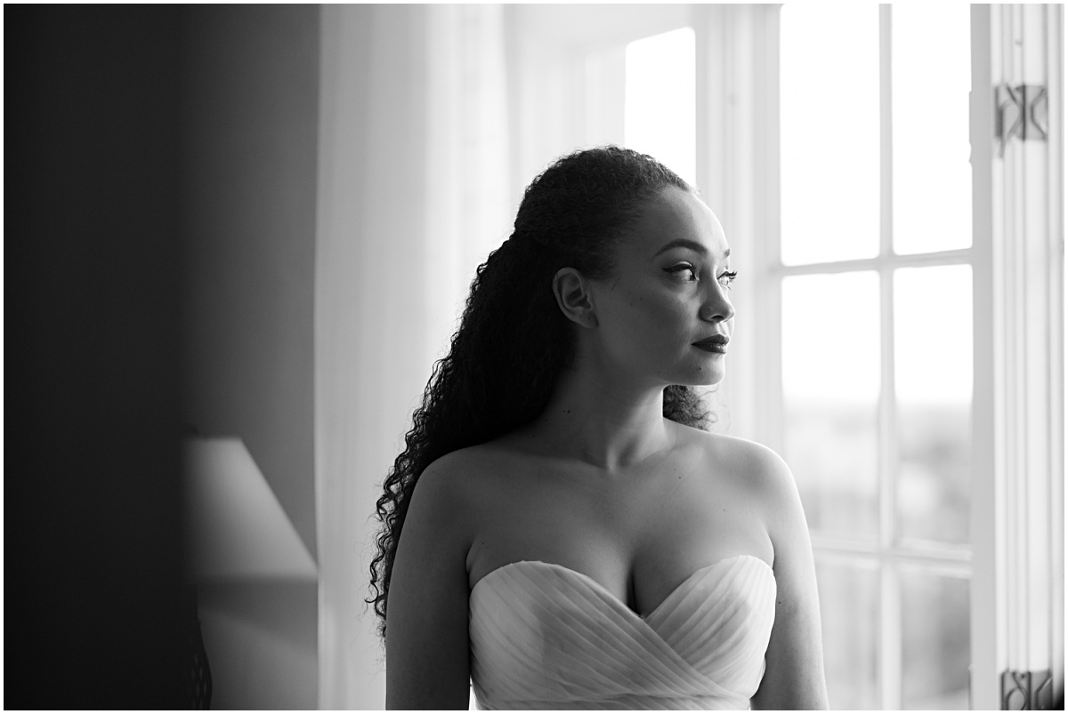 a portrait of the bride looking out the window