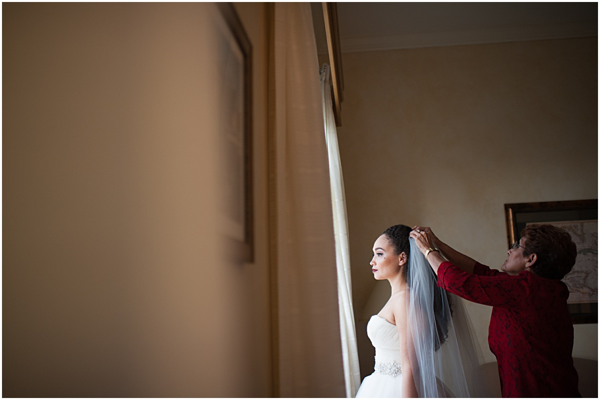 mother putting on the veil of the bride