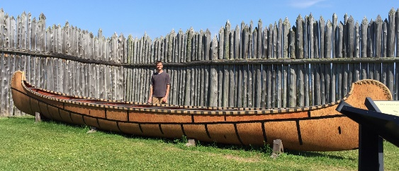 Ryan Collins standing by a Voyageur canoe.