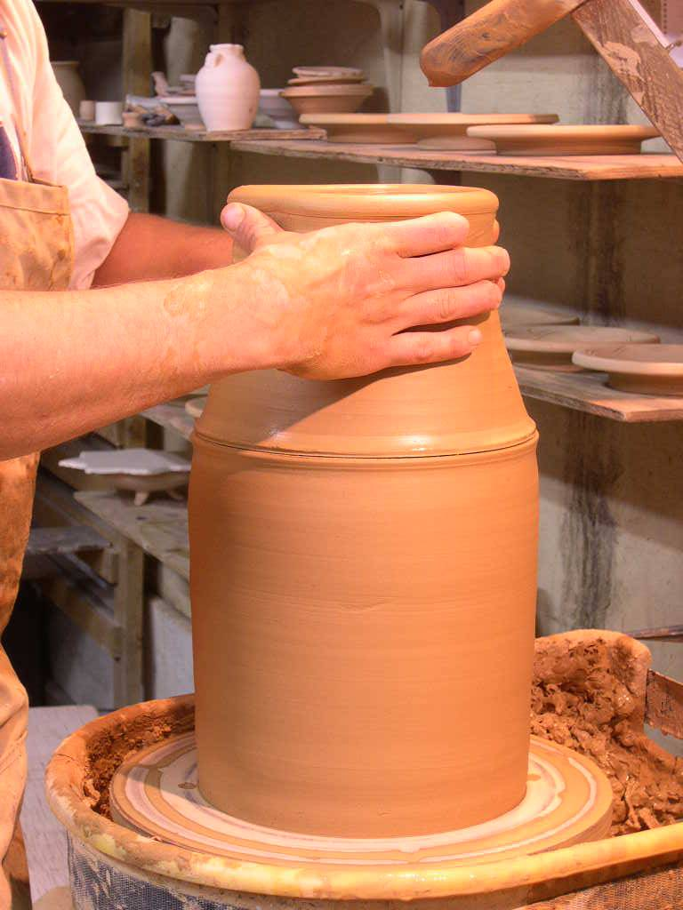 "Here I am adding the ""cap"" that I actually made before I threw the bottom section. I measured the cap before I took it off the wheel with my calipers, then set it aside. The cap is slightly smaller than the bottom section. One advantage to capping is that the clay is still wet and can still be stretched and thrown. The other advantage is that the torque in the clay, or the throwing lines are in the same direction in both sections."