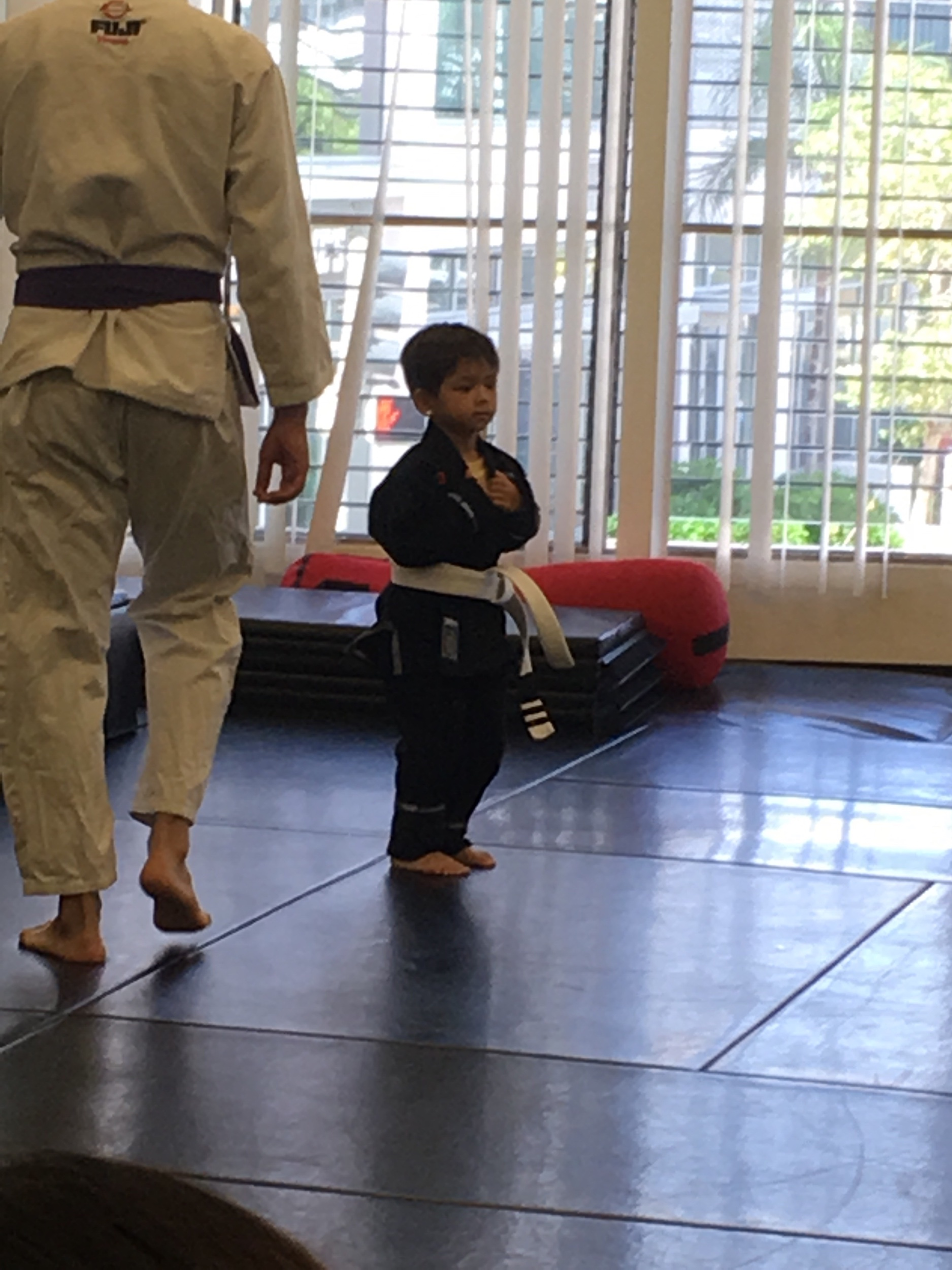 This guy pumped on his big boy black Gi. He had to rock a infant Gi since he was so young and small.  He chose black. Now his Gi is legit and not a baby one, with half sleeves and pants. Can tell he's stoked.